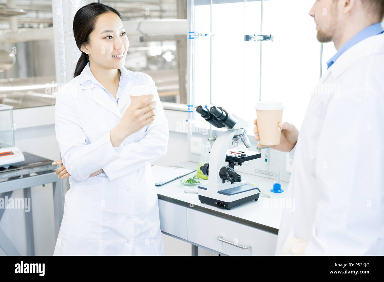 Scientists resting in laboratory with drinks - Stock Image