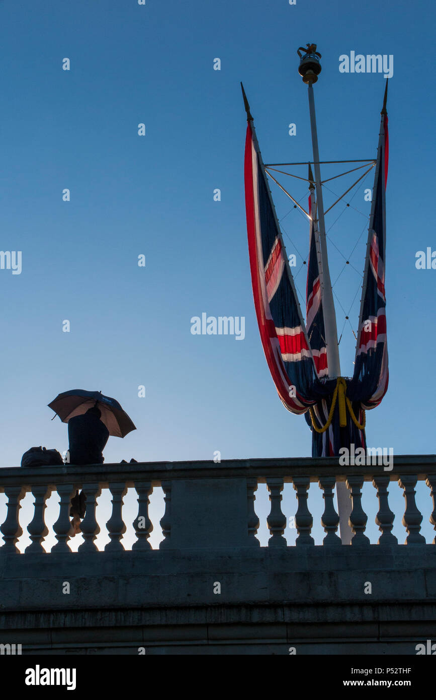 A man sitting on a wall protects himself from the heat and the sun on a hot day in London near Buckingham Palace - Stock Image