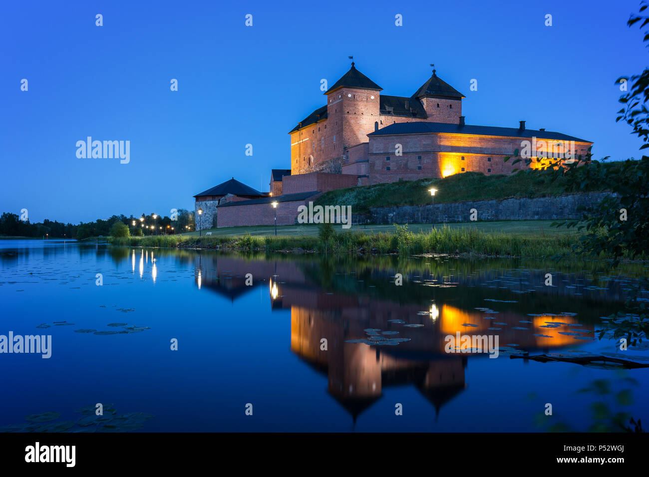Beautiful view of lit 13th century Häme Castle and its reflections on lake Vanajavesi in Hämeenlinna, Finland, at night. Stock Photo