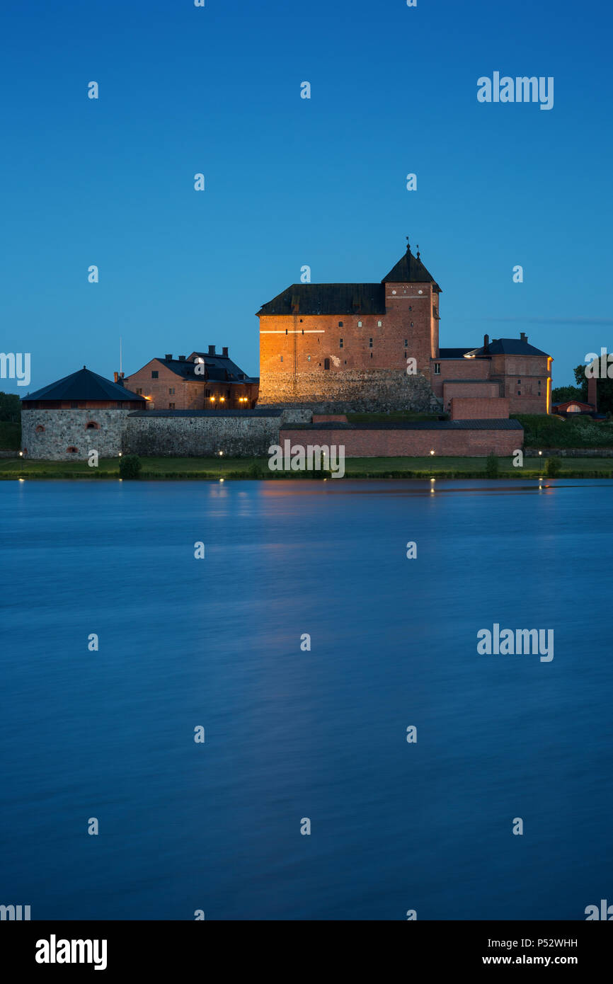 Beautiful view of lit 13th century Häme Castle and lake Vanajavesi in Hämeenlinna, Finland, in the evening. Stock Photo