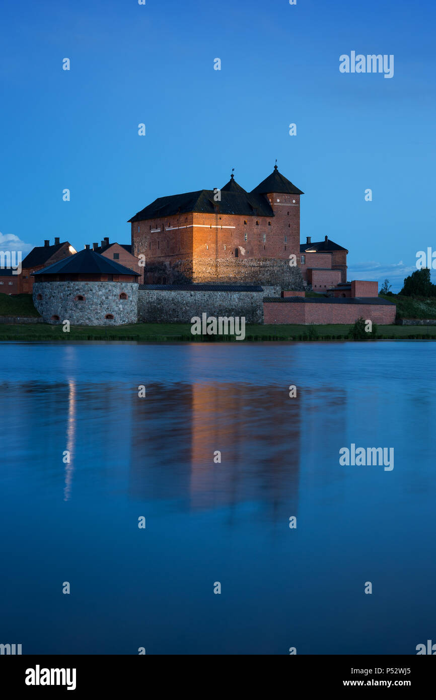 Beautiful view of lit 13th century Häme Castle and its reflections on lake Vanajavesi in Hämeenlinna, Finland, in the evening. Stock Photo