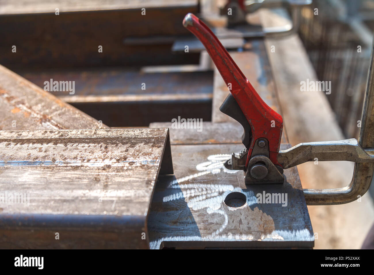 The clamping metal clamp with a red handle is mounted on a metal plate - Stock Image