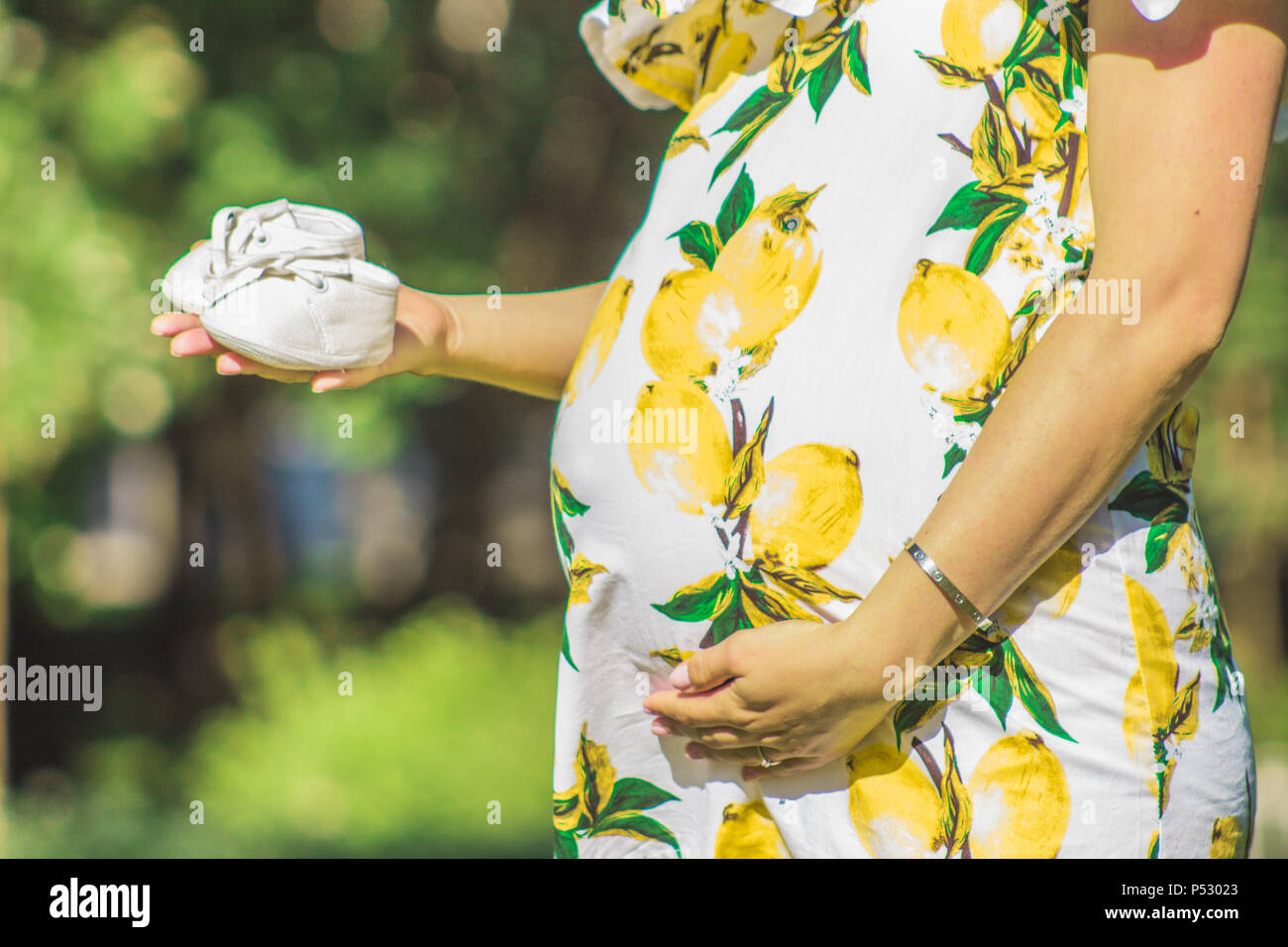 Pregnant girl holding her chopped baby shoes - Stock Image