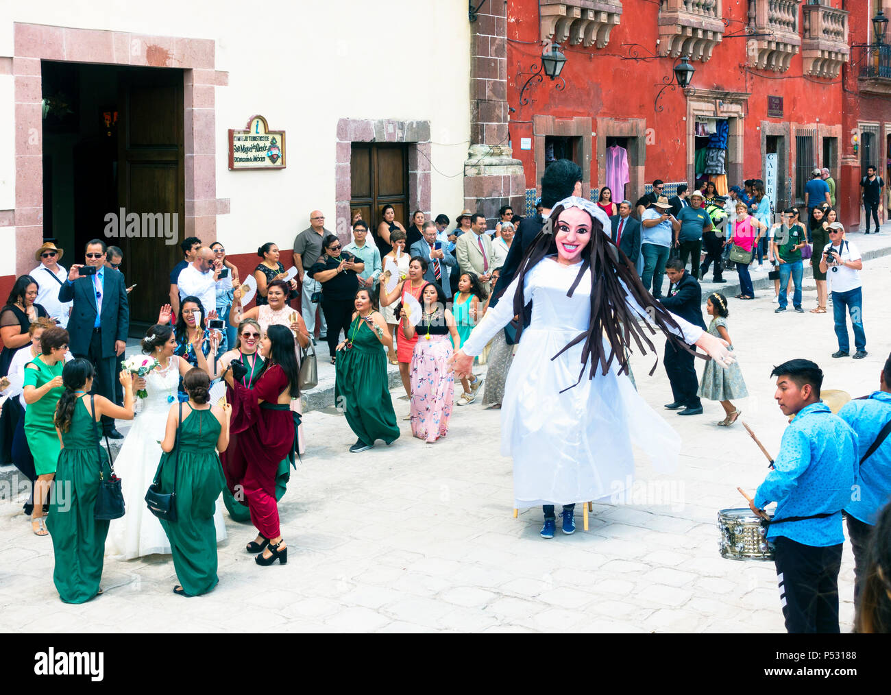 People and a mojigangas dancing in the street at a wedding party at La Jardin in San Miguel de Allende - Stock Image