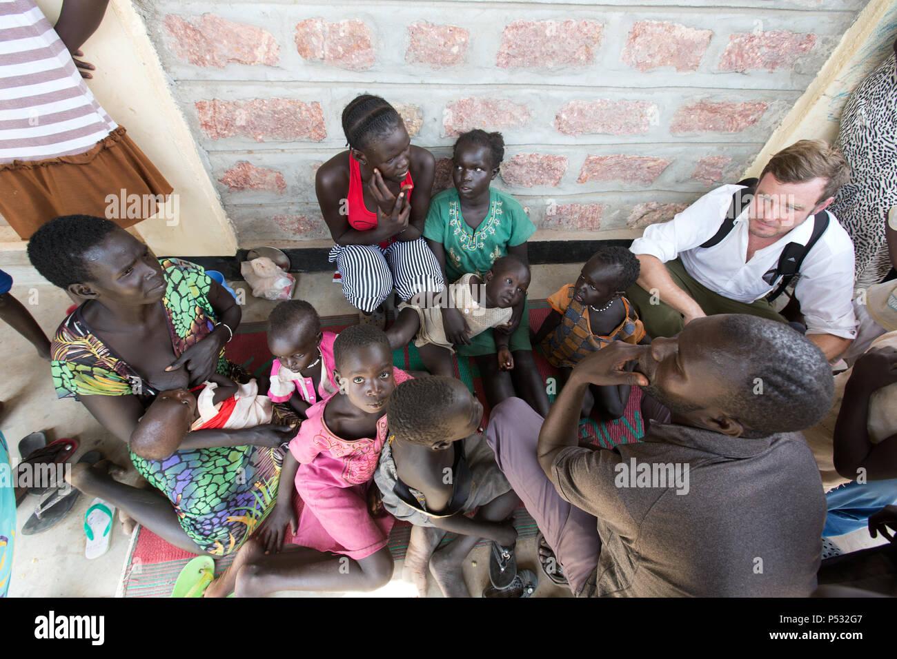 Kakuma, Kenya - Kai Feldhaus, journalist of the Bild newspaper in conversation with new arrivals in the Registration Center Kakuma. - Stock Image