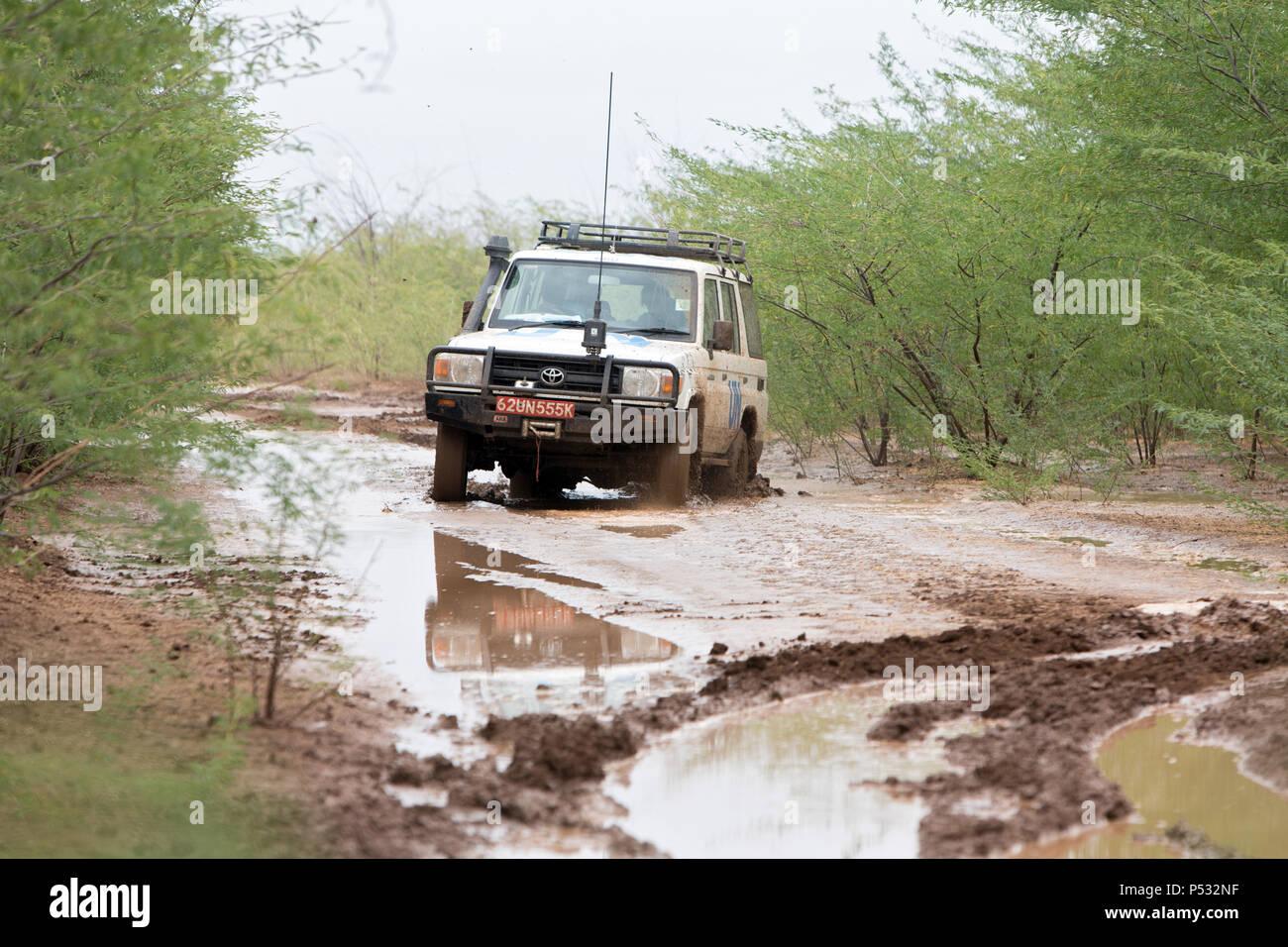 KAKUMA, KENYA - A UN Land Rover drives on a rain-soaked country lane. - Stock Image