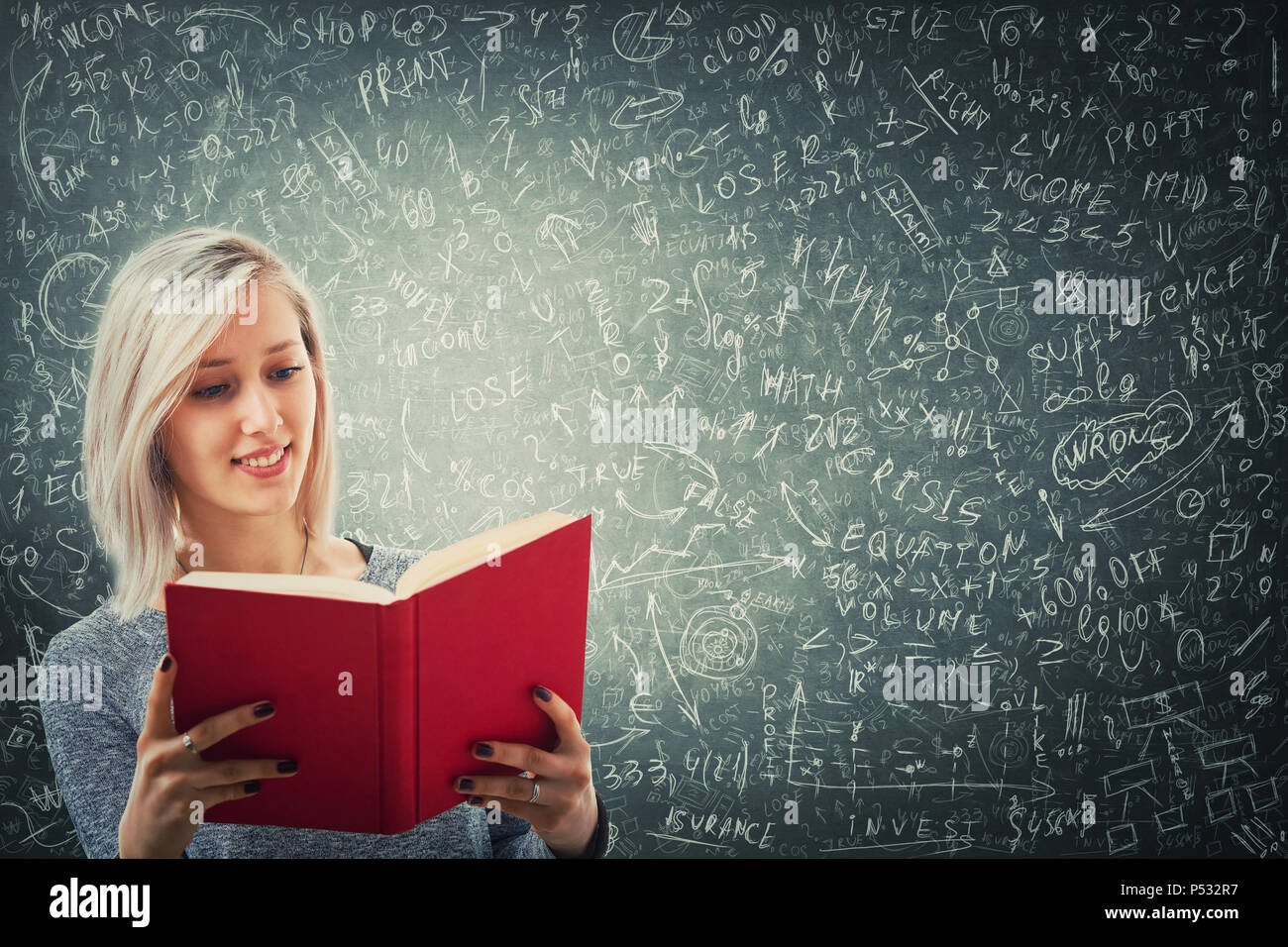 Teacher holding a red book in front of a huge blackboard try to solve hard mathematics calculation, formula and equations. Thinking of project ideas a - Stock Image