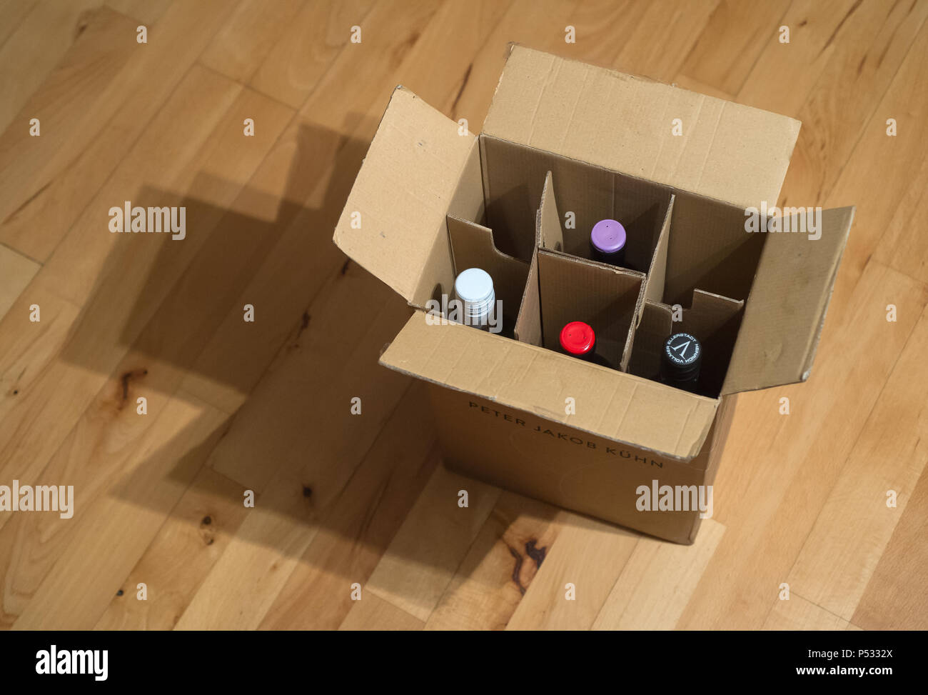 Wine carton with wine bottles on a parquet floor - Stock Image