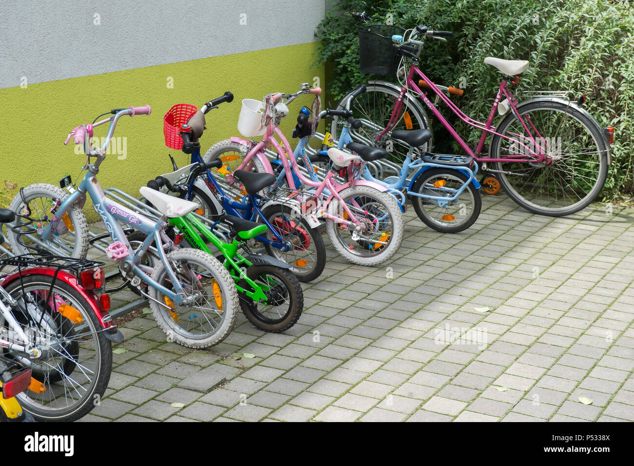 various sizes of bicycles in front of a daycare - Stock Image
