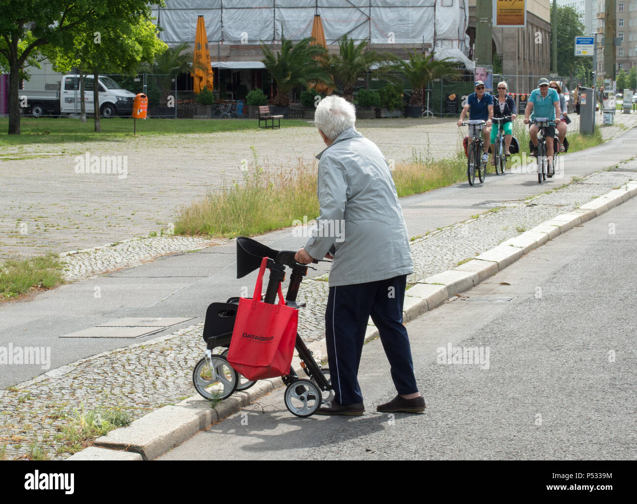 A retiree crossing a road and a bike path - Stock Image