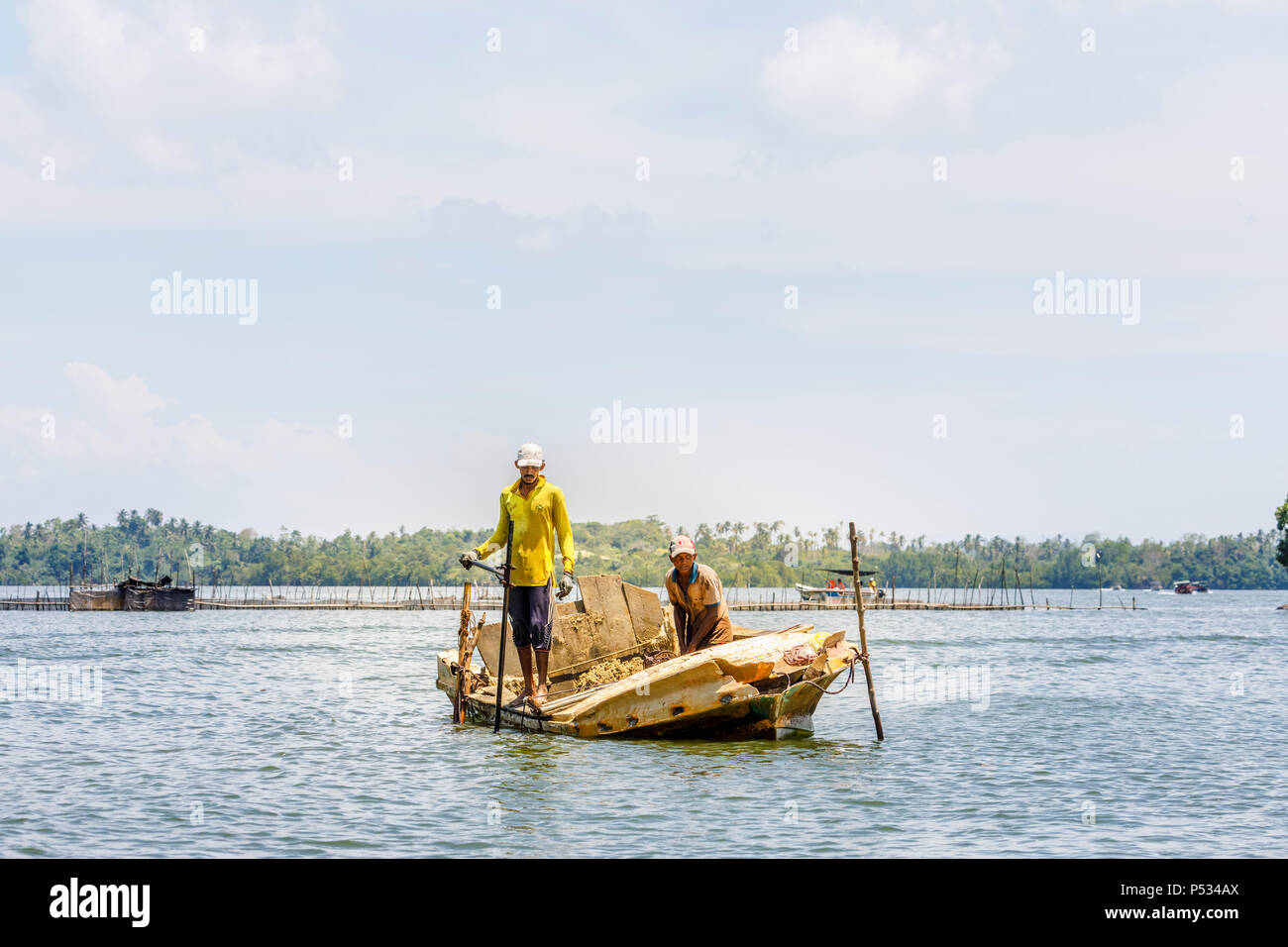 Two local men people illegally excavating sand from a dilapidated boat from the Madu River, Madu Ganga wetlands, south-west Sri Lanka - Stock Image