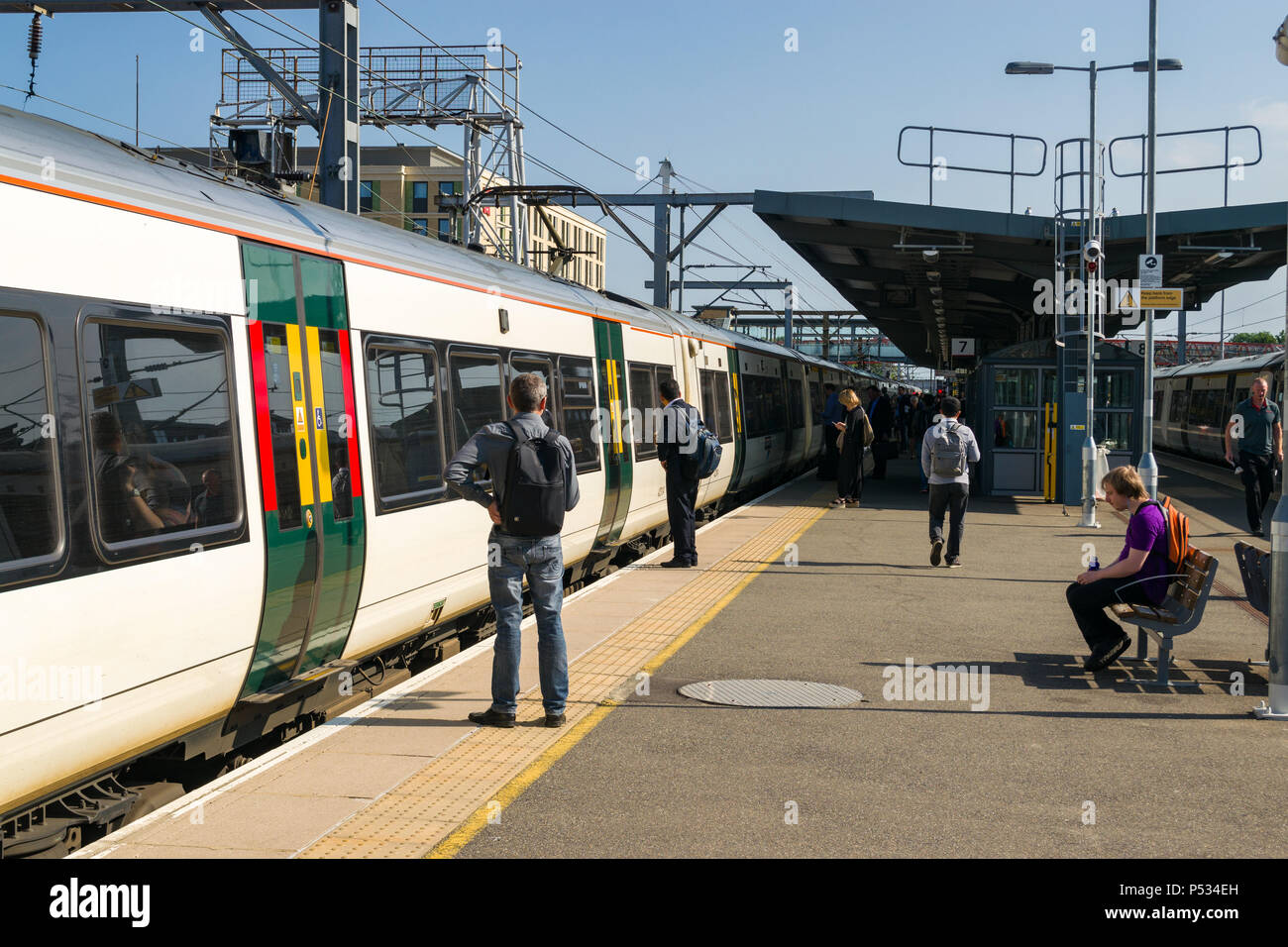 Passengers wait on a platform to board a train from Cambridge train station on a sunny Summer morning - Stock Image