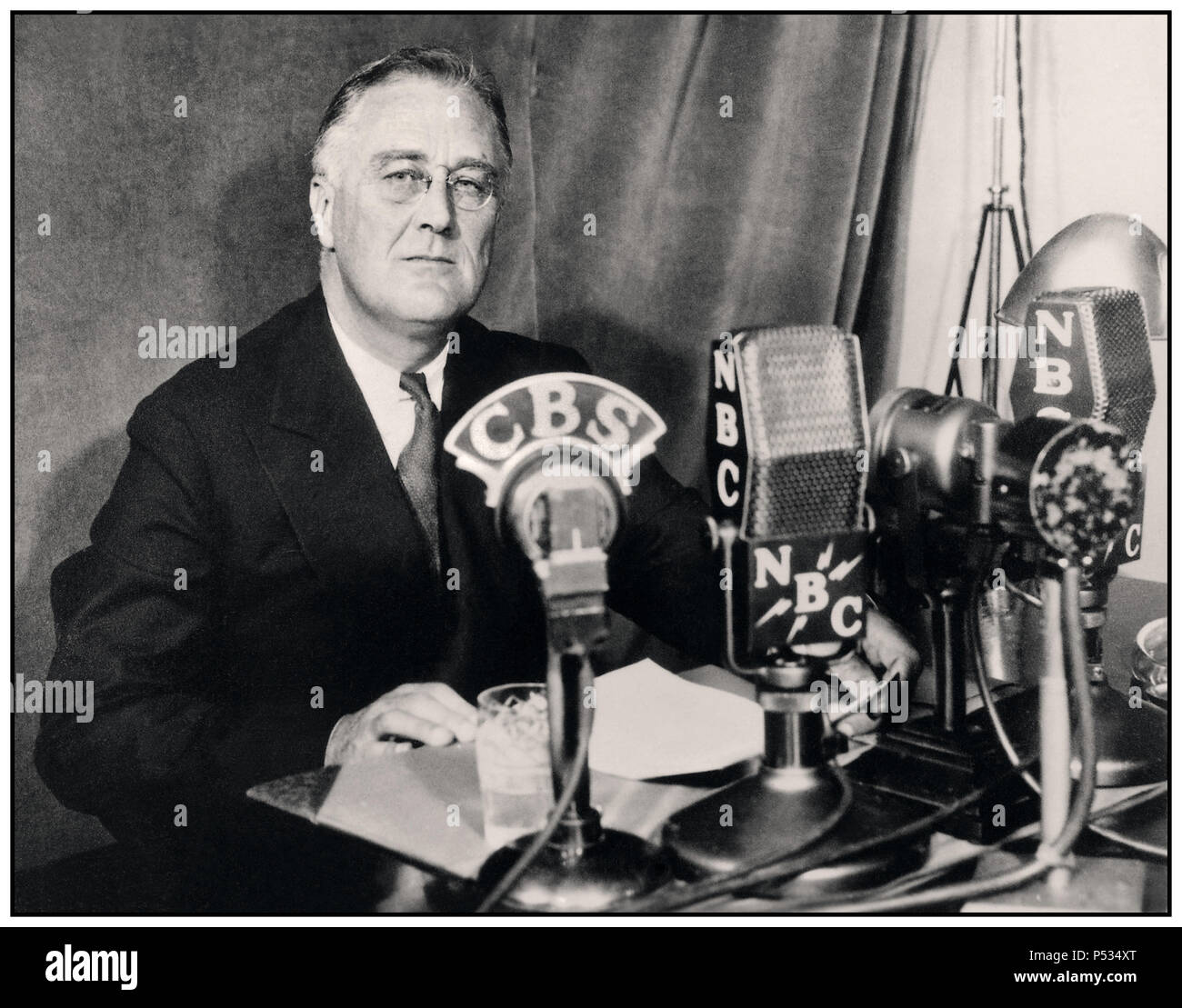 """Vintage 1930's Image of FDR Franklin D. Roosevelt giving a radio broadcast (""""fireside chat"""") September 1934. Franklin Delano Roosevelt Sr., often referred to by his initials FDR, was an American statesman and political leader who served as the 32nd President of the United States from 1933 until his death in 1945. - Stock Image"""