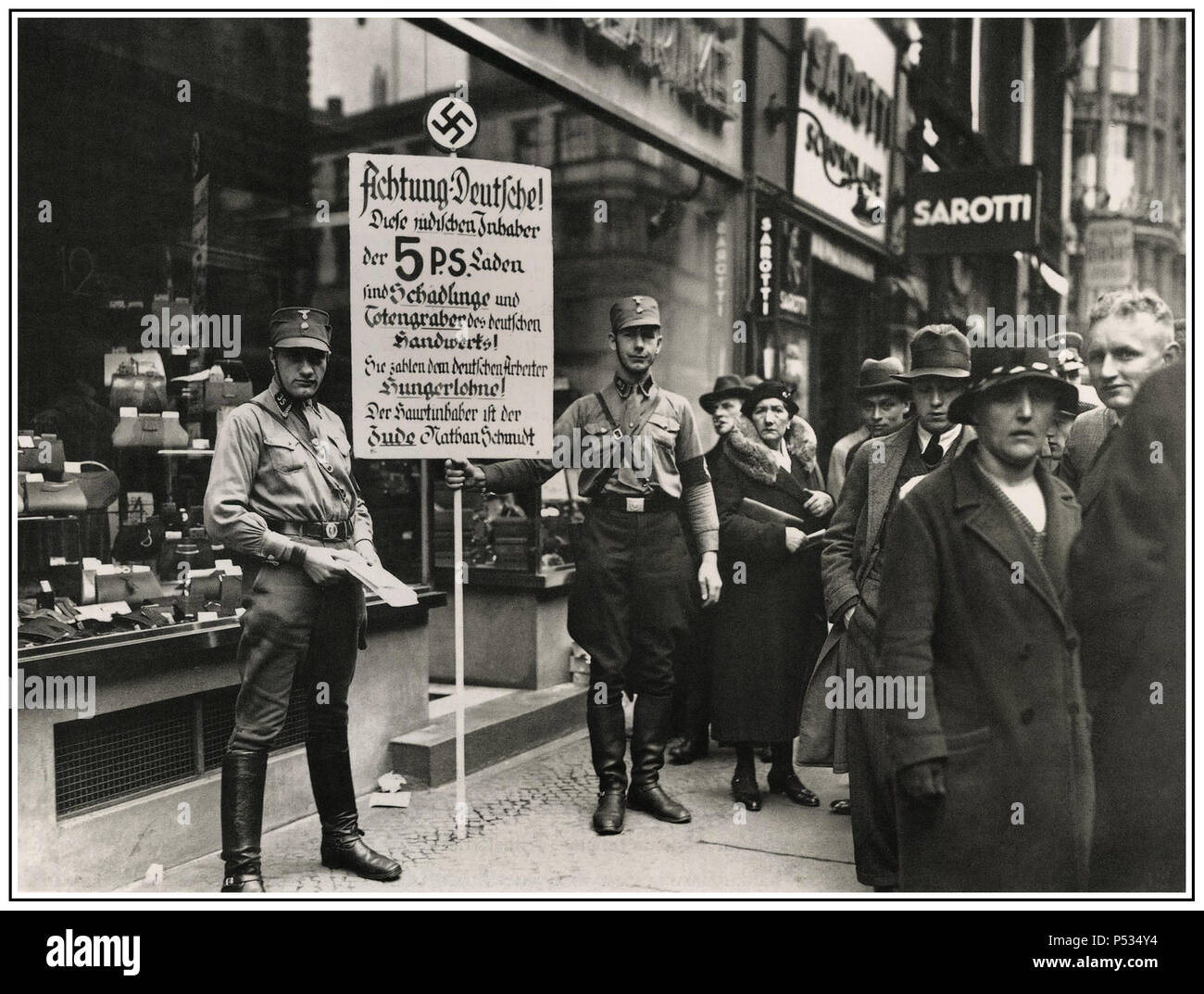 """Vintage B&W anti-Jewish racist inflammatory image of SA Sturmabteilung or """"Brownshirts"""" storm detachment members calling for the boycott of Jewish shops in Friedrichstraße, Berlin; April 1, 1933. The sign with Nazi swastika emblem says: """"Germans, Attention! This shop is owned by Jews. Jews damage the German economy and pay their German employees starvation wages. The main owner is the Jew Nathan  Schmidt."""" - Stock Image"""
