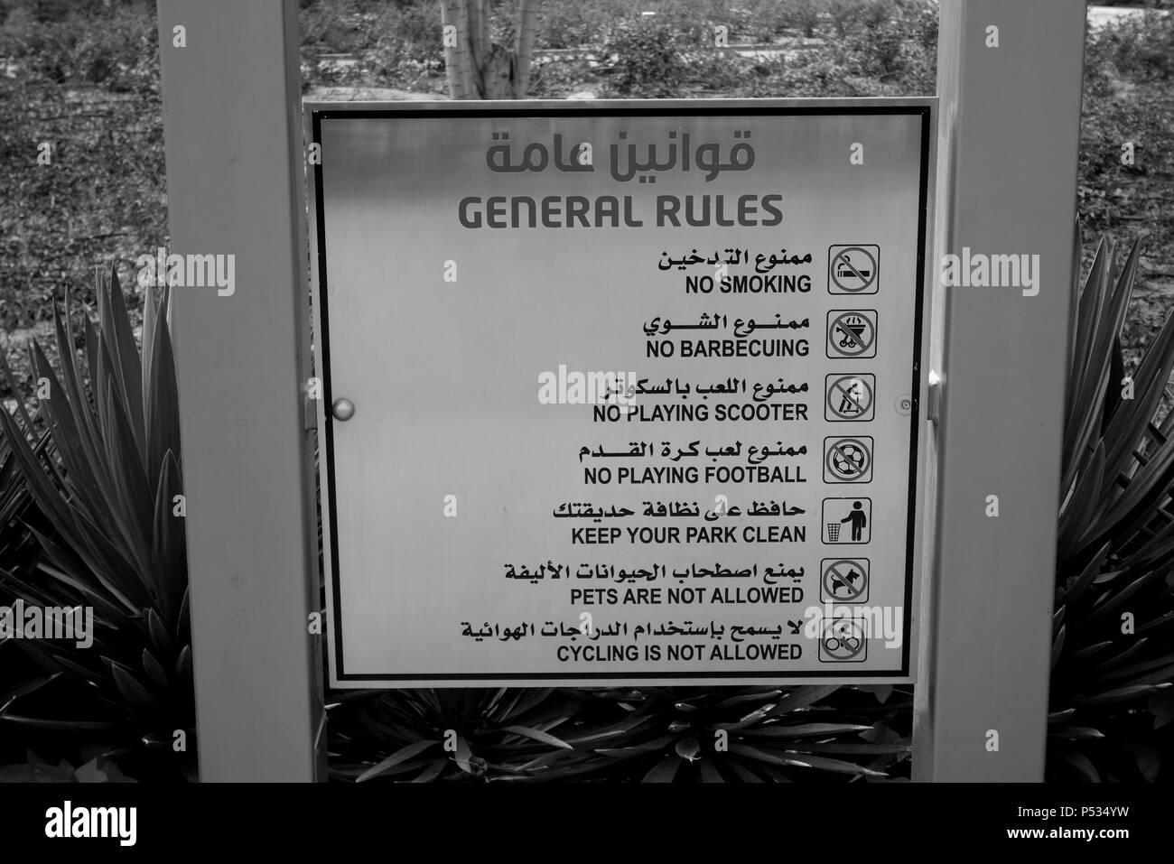 List of Park rules and regulations in English and Arabic displayed in a public park, Kuwait City, Kuwait, Arabian Gulf, Middle East - Stock Image