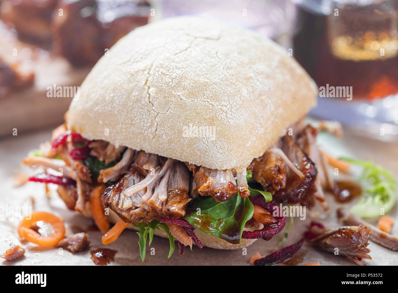 Pulled pork bun with lettuce and barbecue sauce - Stock Image
