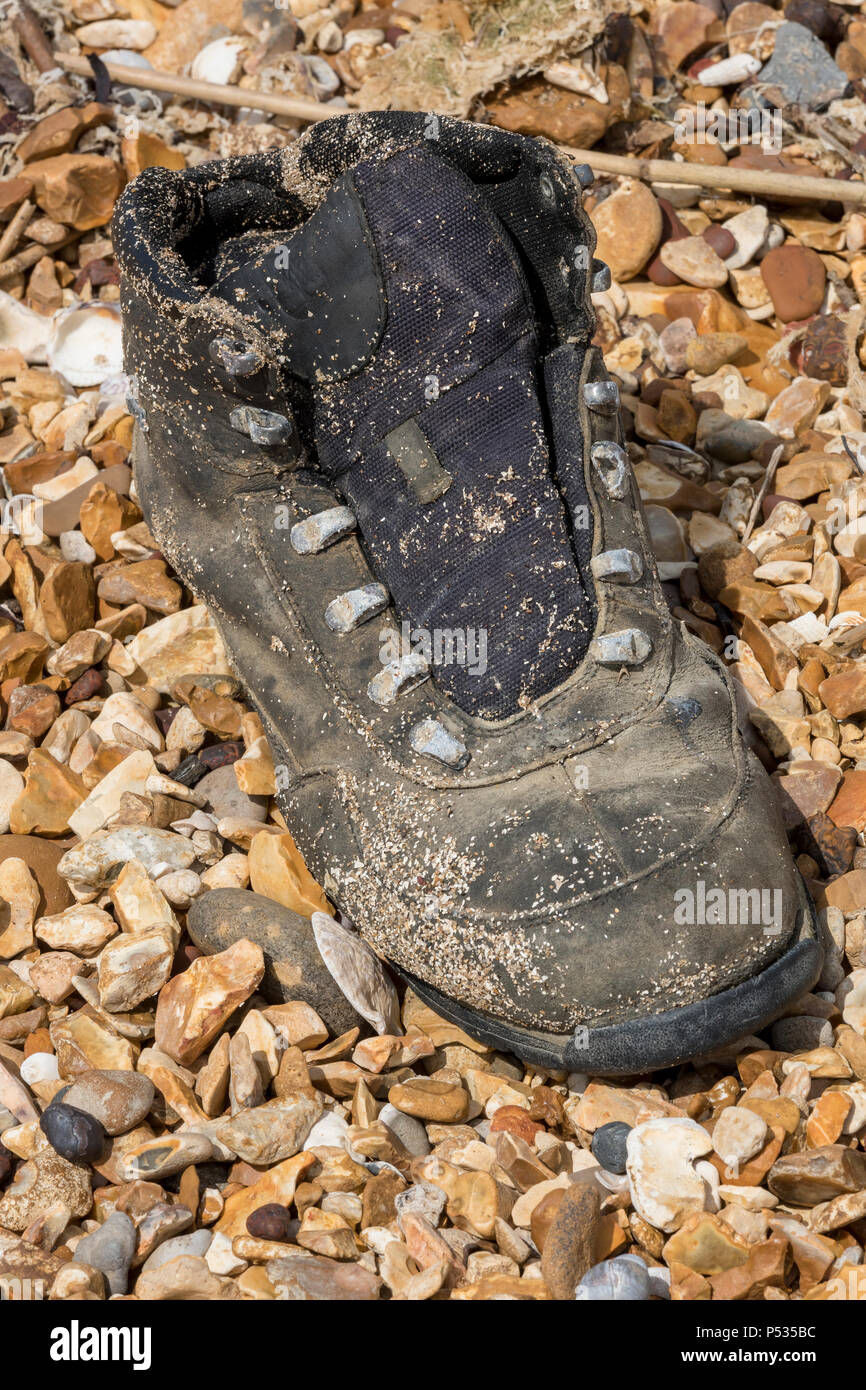 an old boot washed up on the beach on the isle of wight. - Stock Image