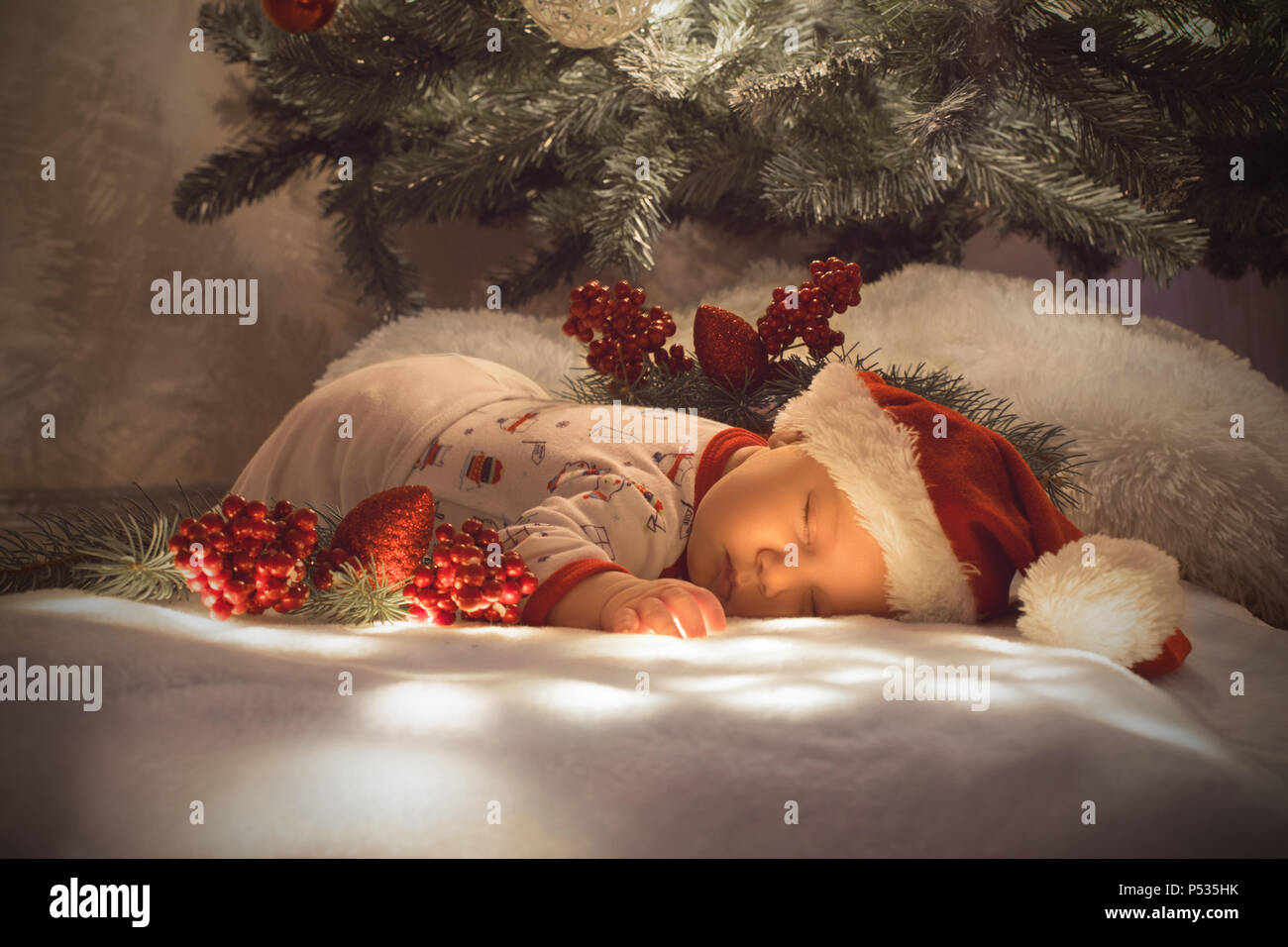 0bce8b3ad31e Newborn baby boy sleeping under Christmas tree near lot of decorations. Wearing  Santa´s