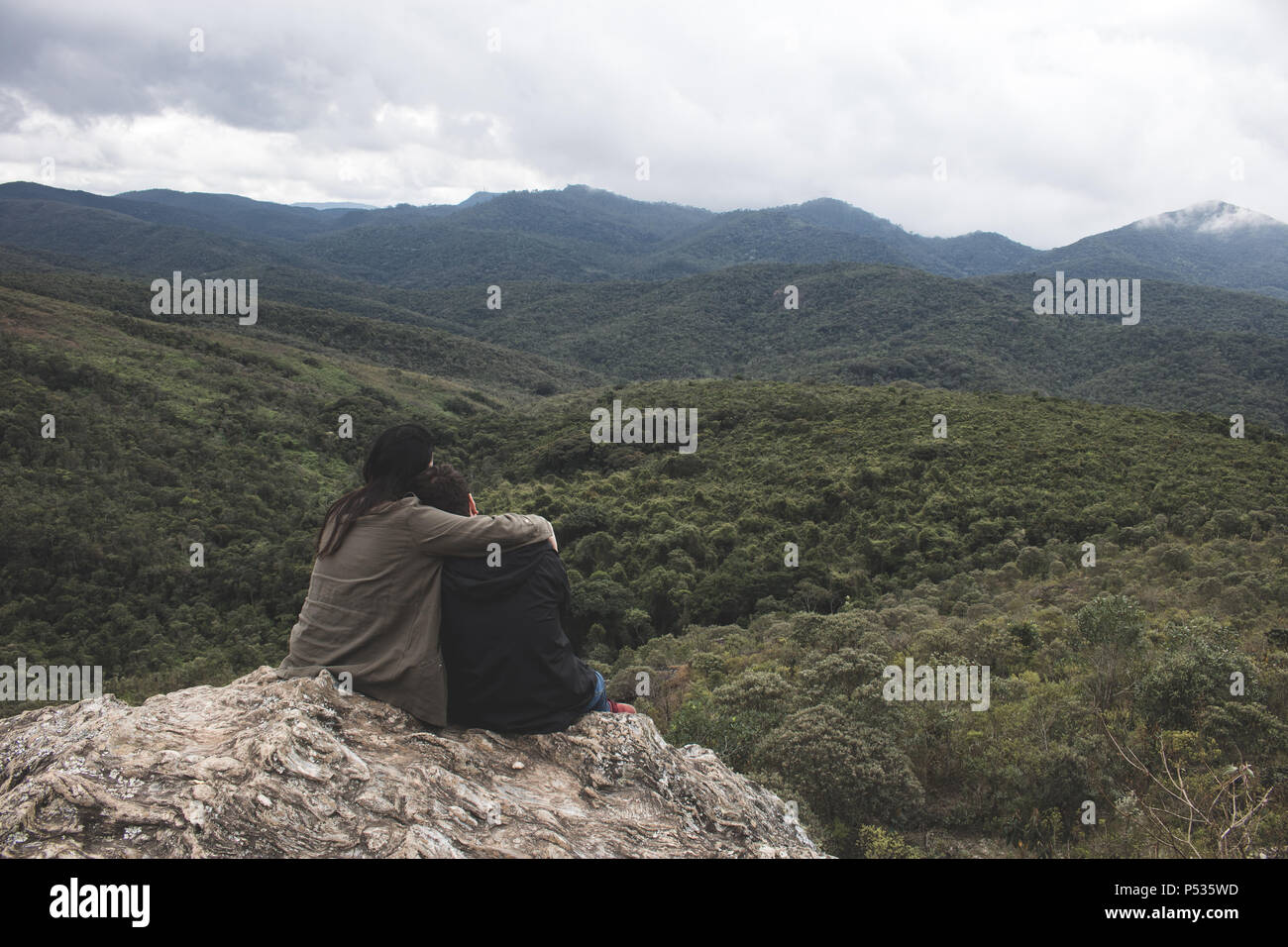 romantic couple sharing complicity with a marvelous mountain view - Stock Image