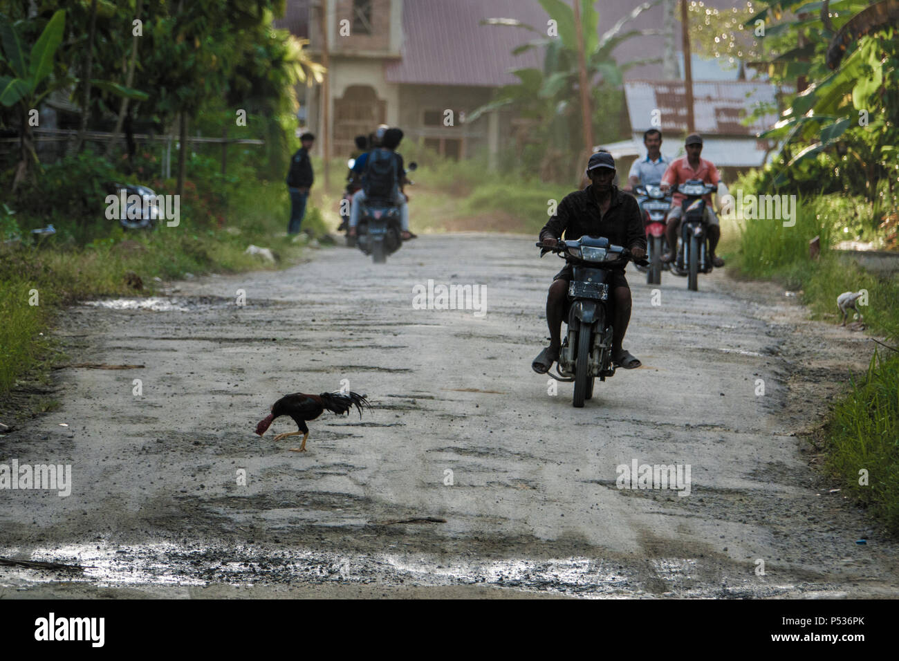 People commuting on motor scooters along potholed road in Afulu, Nias Island, Sumatra, Indonesia - Stock Image