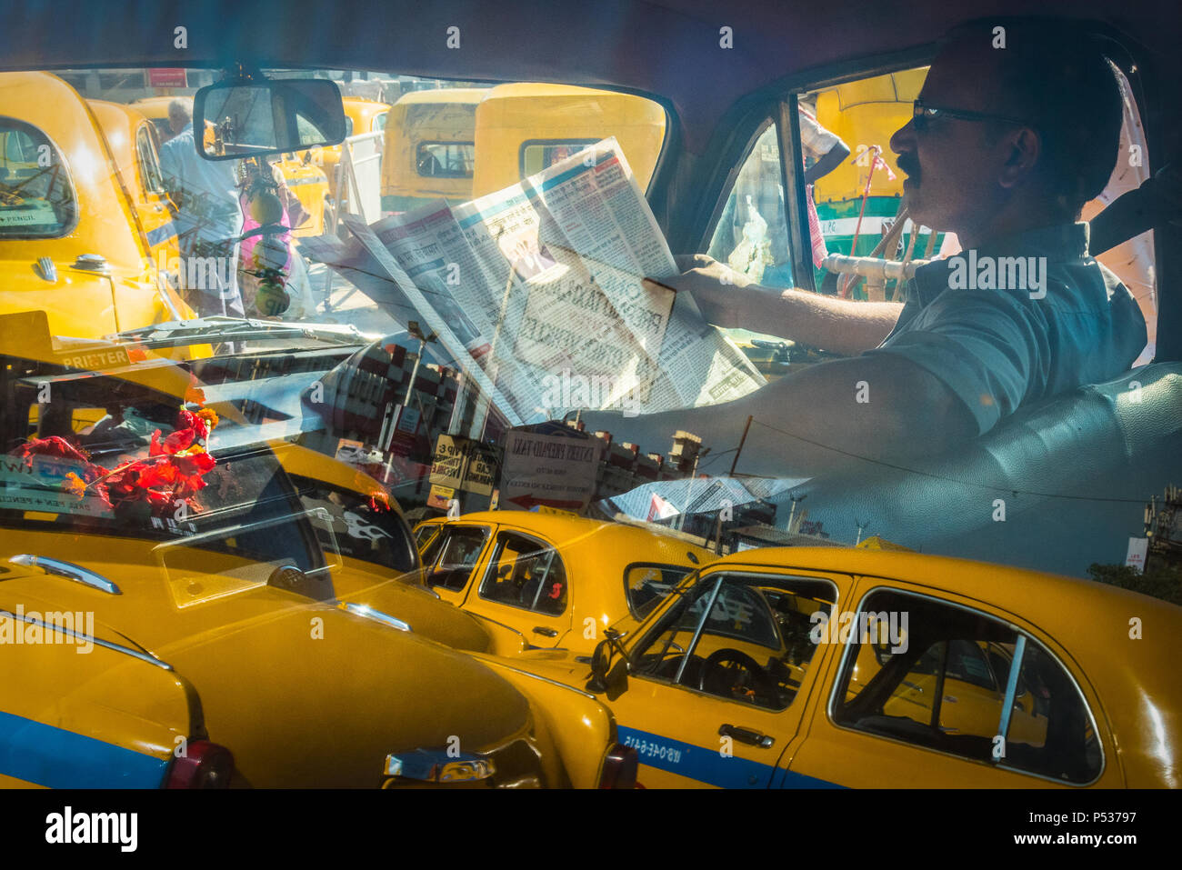 A taxi driver in a queue of Hindustan Ambassadors, the reflections of other cars shining on the windows. Kolkata, India. - Stock Image