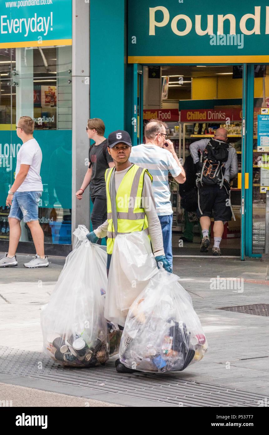 A woman collecting litter form litter bins in Birmingham City Centre, Birmingham, England, UK - Stock Image
