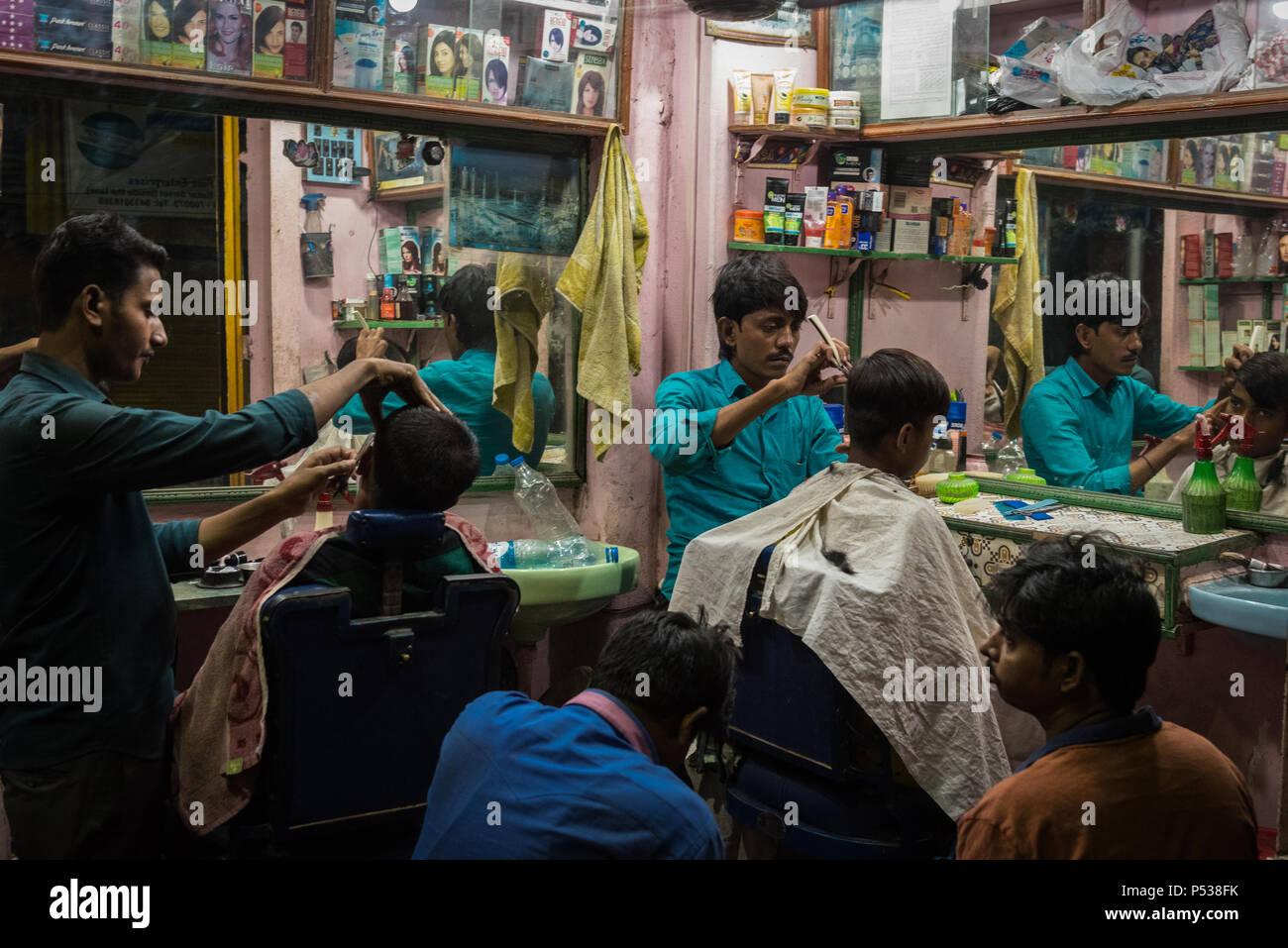 Barbers cutting hair at an outdoor barbershop in Kolkata, India
