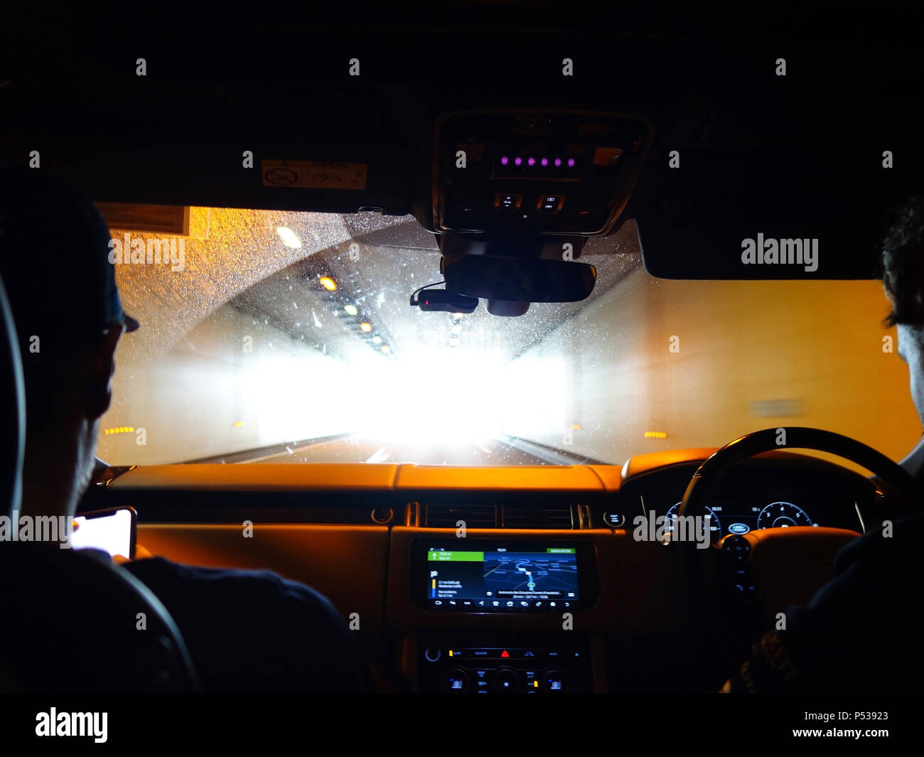 Two guys driving in their Range Rover through a long tunnel in France - Stock Image