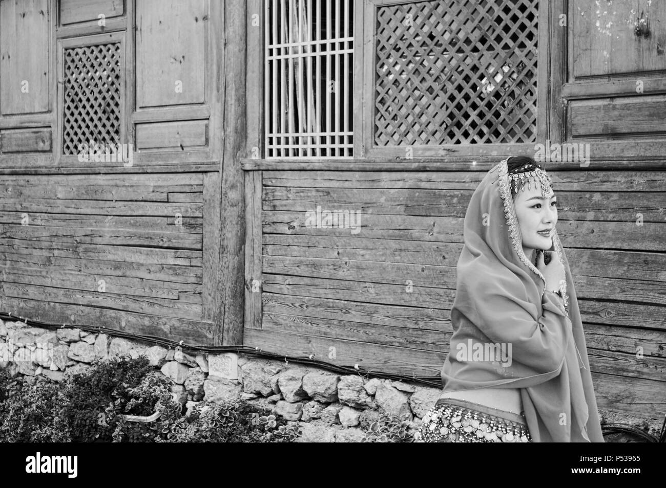 Lijiang, Yunnan, China - 29 December 2017: Isolated chinese model and wooden background - Stock Image