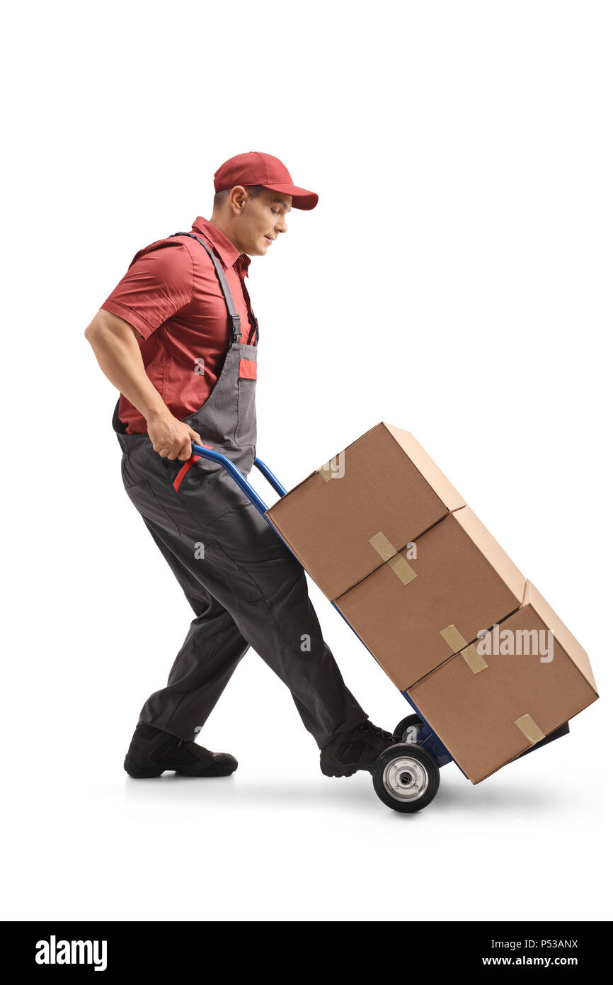 Full length profile shot of a mover with a hand truck loaded with cardboard boxes isolated on white background - Stock Image