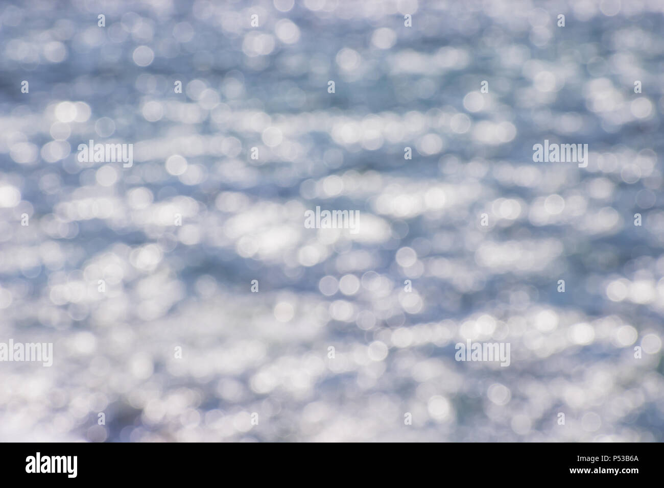 Beautiful abstract background bokeh sun light reflections on blue river surface water - Stock Image