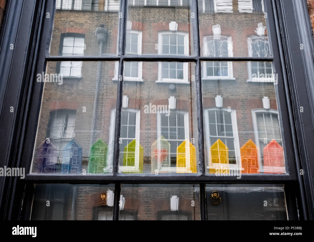Window of Huguenot house on Princelet Street, Spitalfields, London, showing reflection of buildings opposite and quirky rainbow coloured model houses - Stock Image