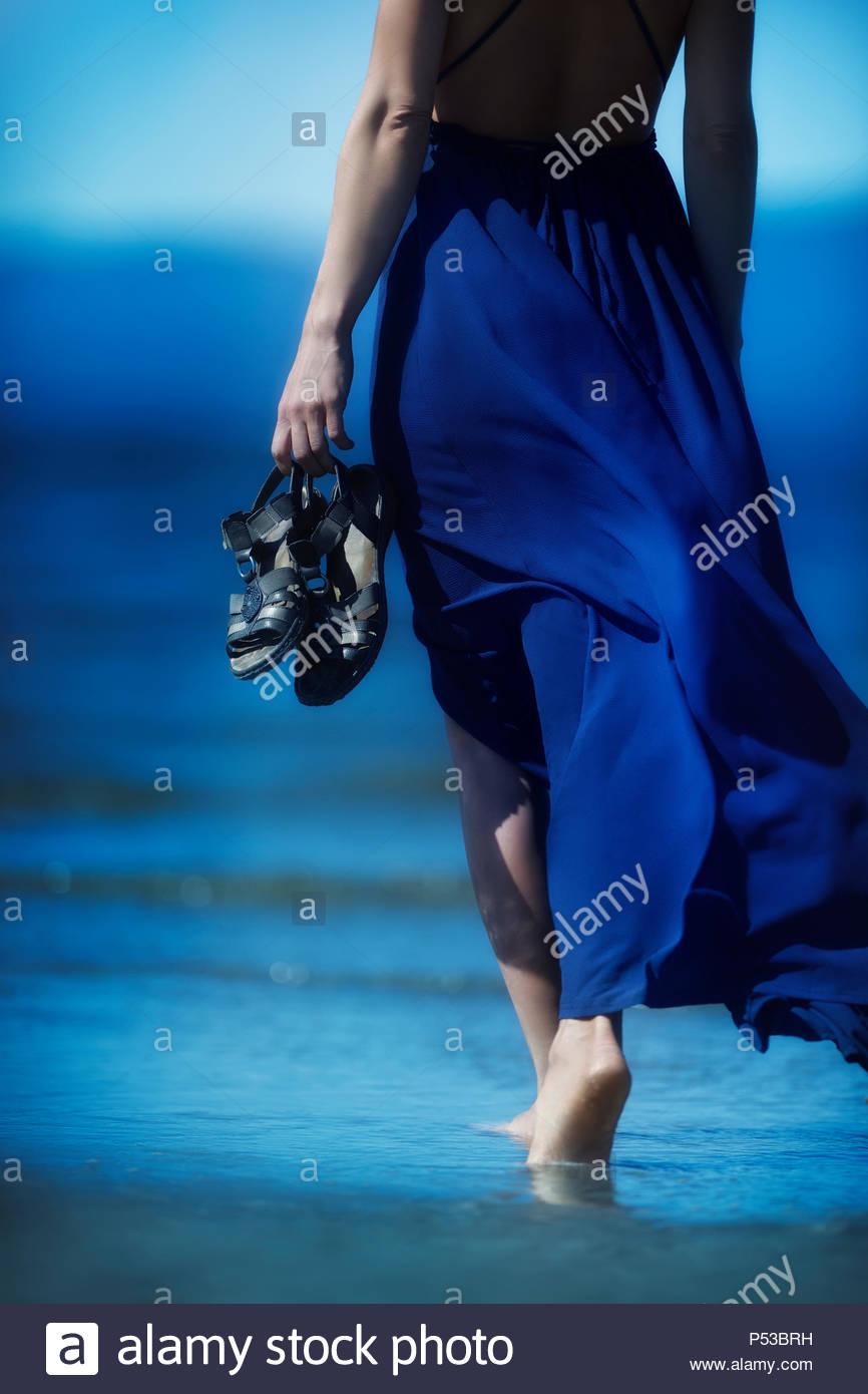 Woman in blue summer dress blowing in the wind walking barefoot on ocean beach  sand towards 06f9fdedcf2c