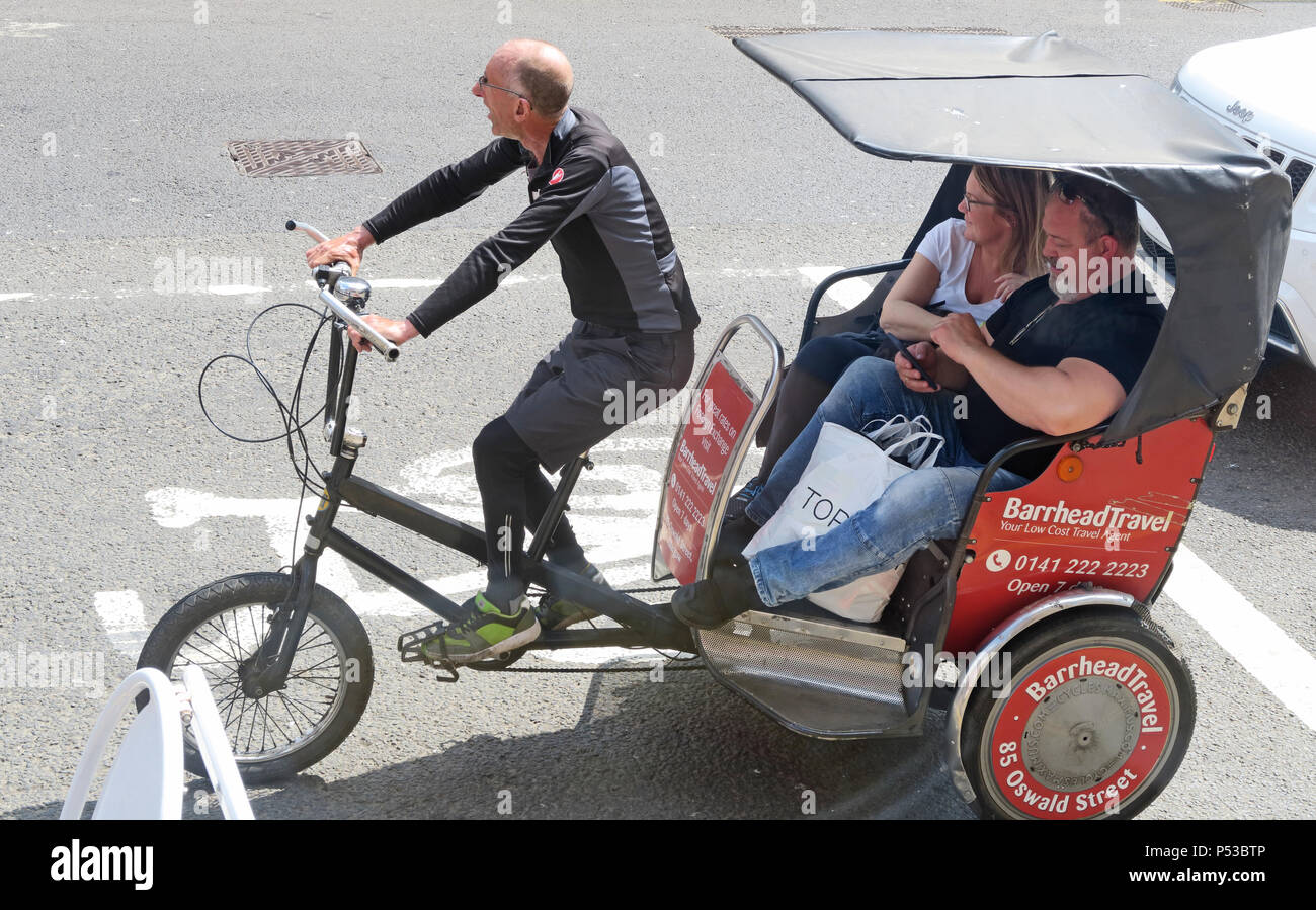 Glasgow Cycle Rickshaw rider, with two large people as customers, Scotland, UK - Stock Image