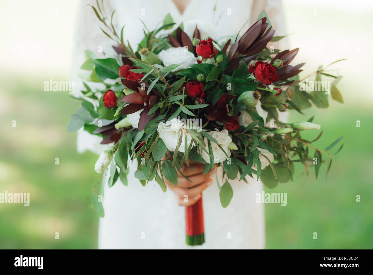 Wedding Bouquet Of Red Flowers And Greenery In The Hands Of The