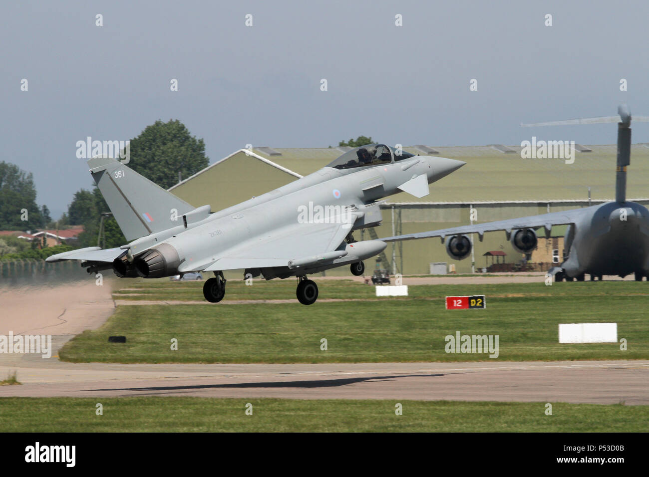 Royal Air Force Typhoon FGR4 over the runway and about to land at RAF Coningsby, it's home base. Note the USAF C-17 transport parked behind. - Stock Image