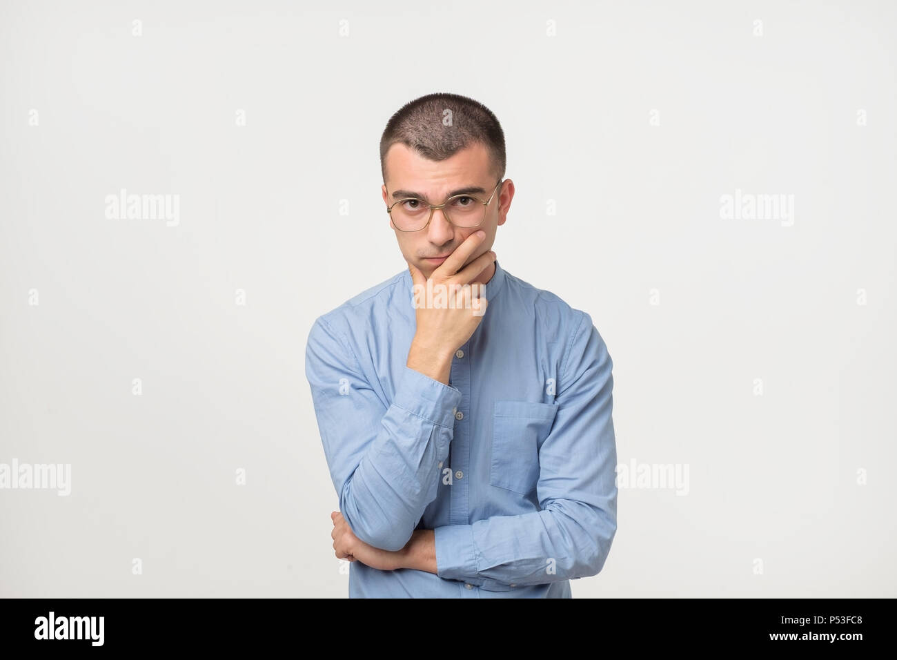 Young man in blue shirt standing disorientated bewildered isolated on gray wall background. Decision making concept. Human facial expression emotions - Stock Image
