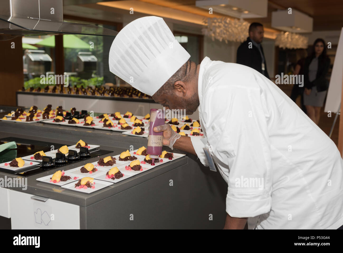 Pastry Chef adding the final touches to his desserts. - Stock Image
