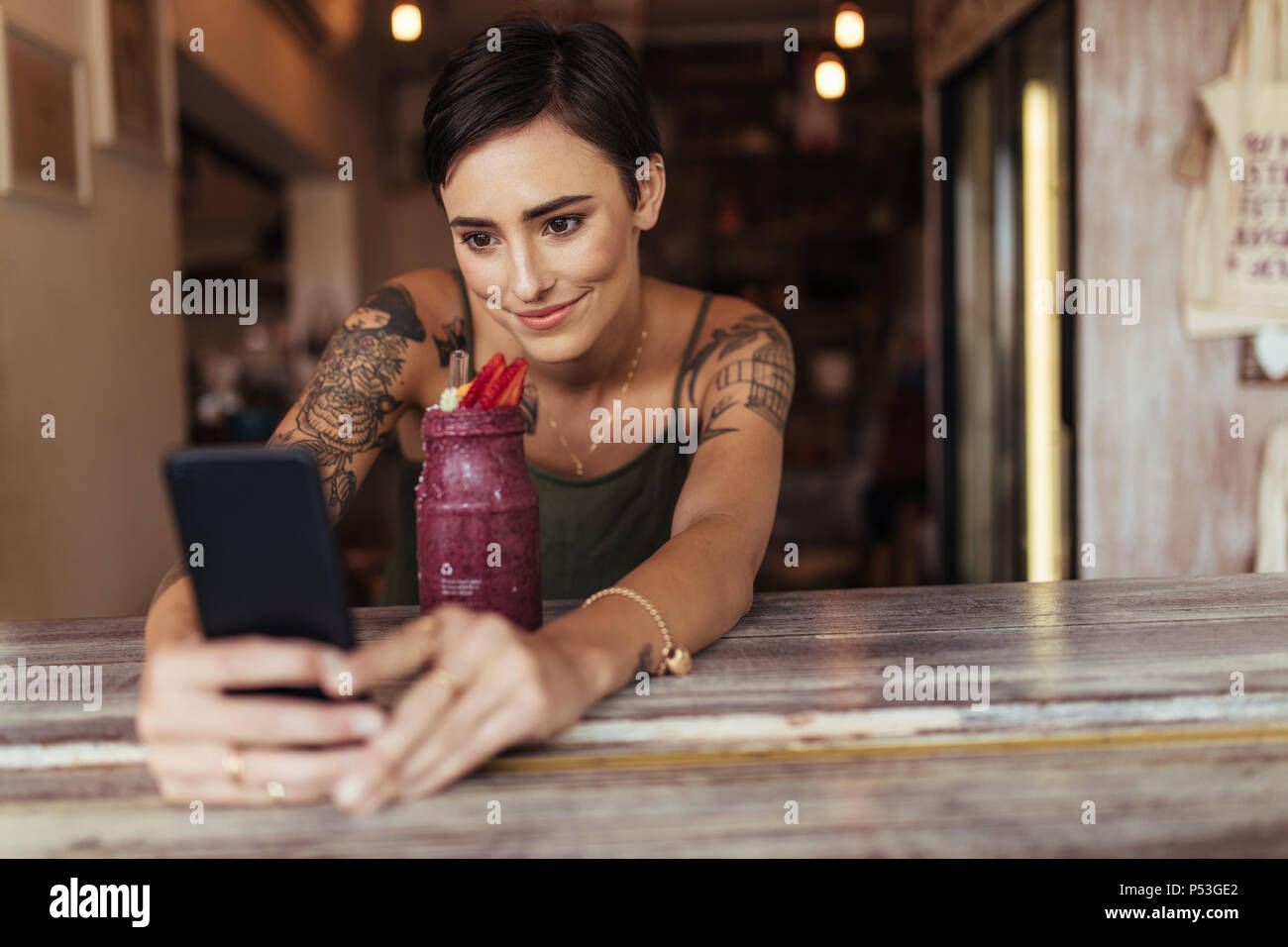 Woman taking a selfie with a smoothie placed in front of her using a mobile phone for her food blog. Food blogger shooting photos for her blog at home - Stock Image