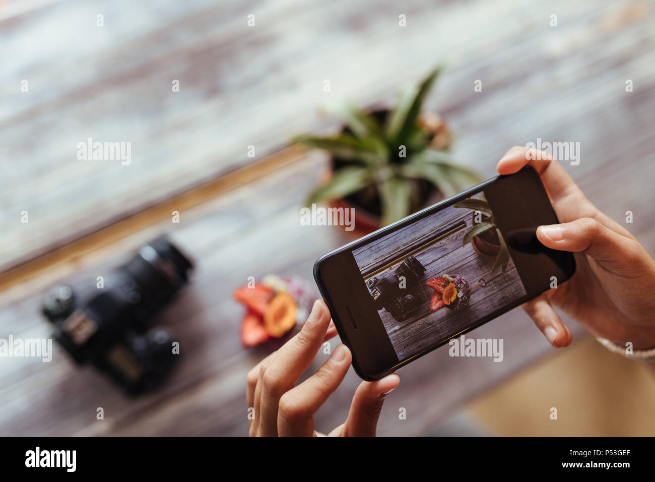 Close up of a woman taking photo of fruits in a bowl using a mobile phone for her food blog. Blogger capturing photo of a fruit bowl placed beside a c - Stock Image