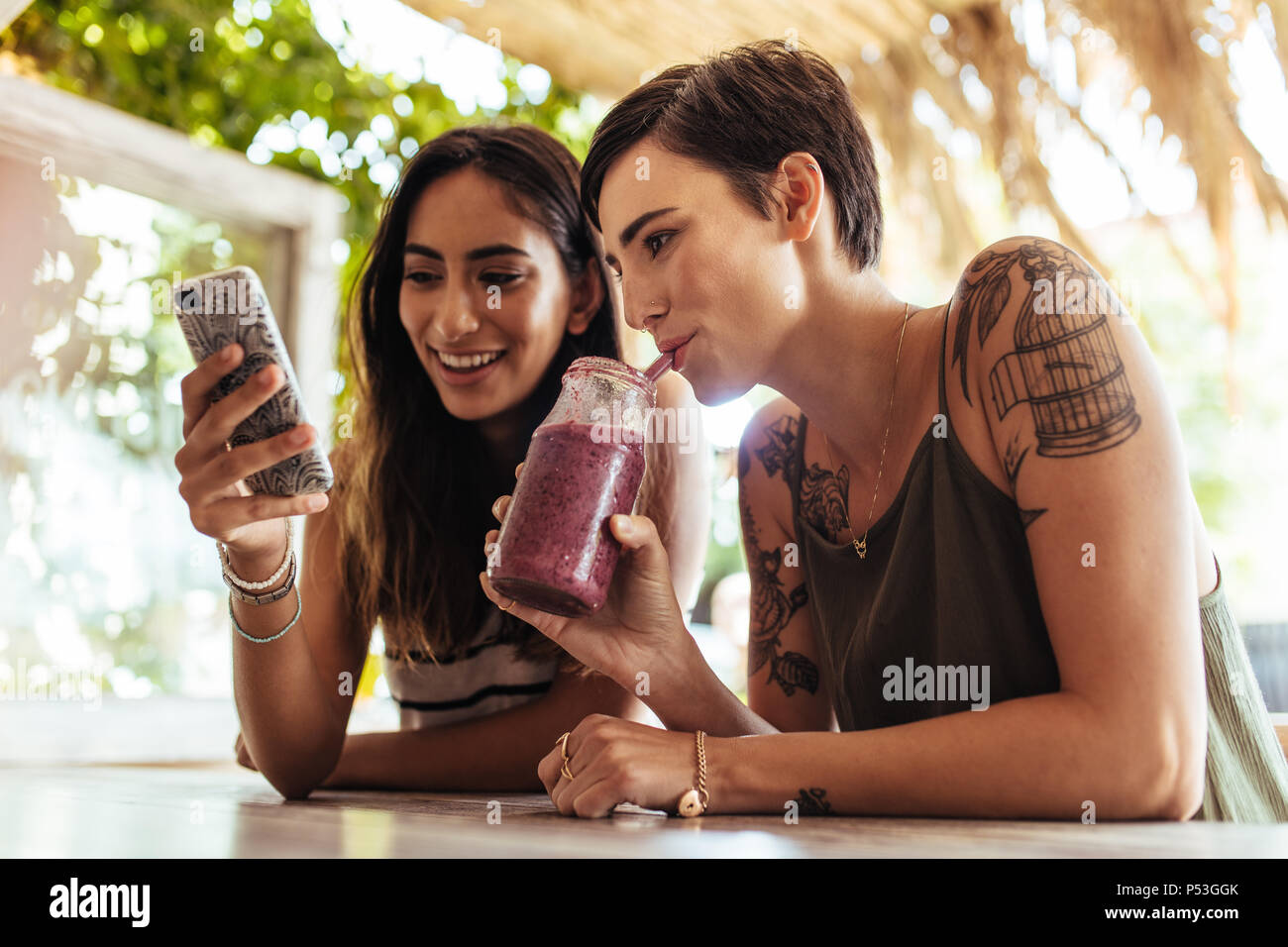 Close up of two women sitting at a restaurant looking at mobile phone. Woman showing mobile phone while another woman enjoys a smoothie. - Stock Image