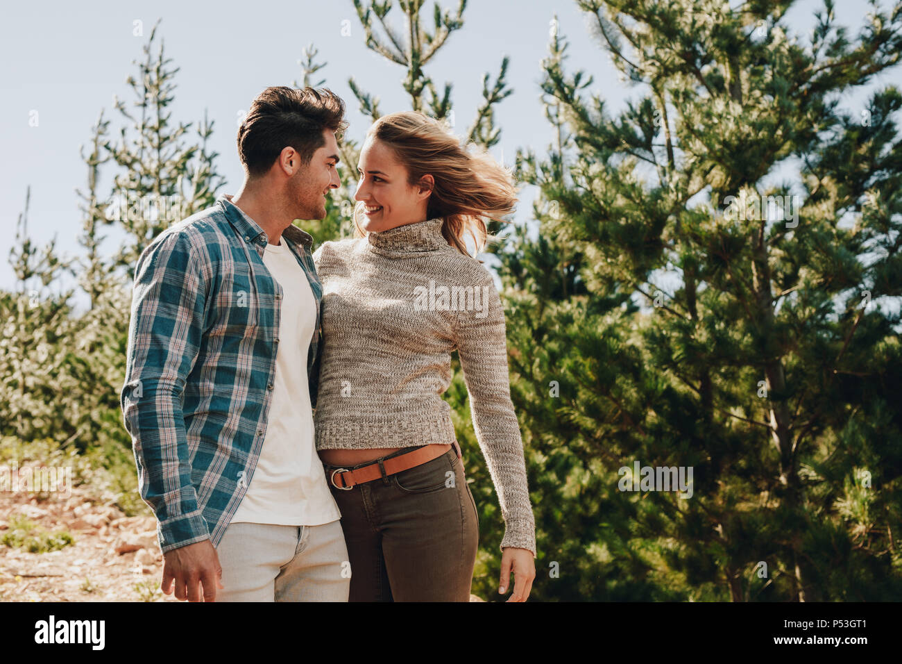 Loving young couple looking at each other and smiling. Man and woman standing outdoors on mountain trail during hiking. - Stock Image