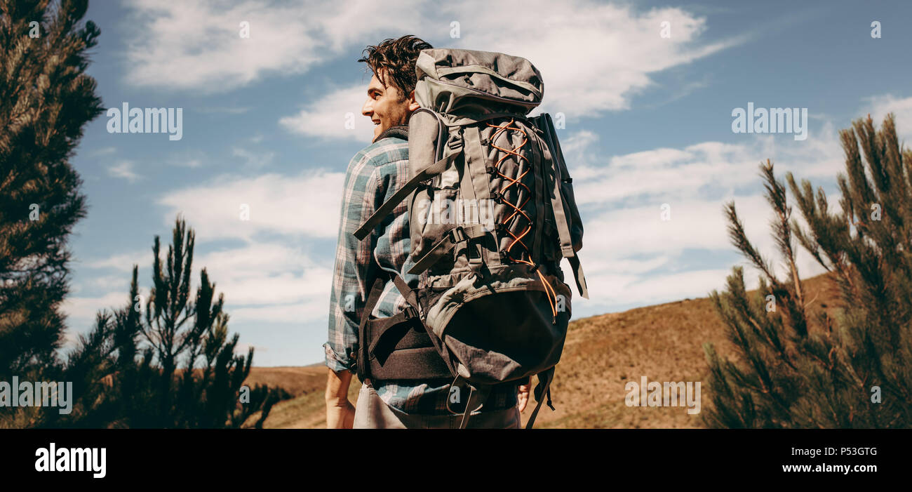 Rear view shot of happy young man with backpack going on a camping. Caucasian male hiker on mountain looking away and smiling. - Stock Image