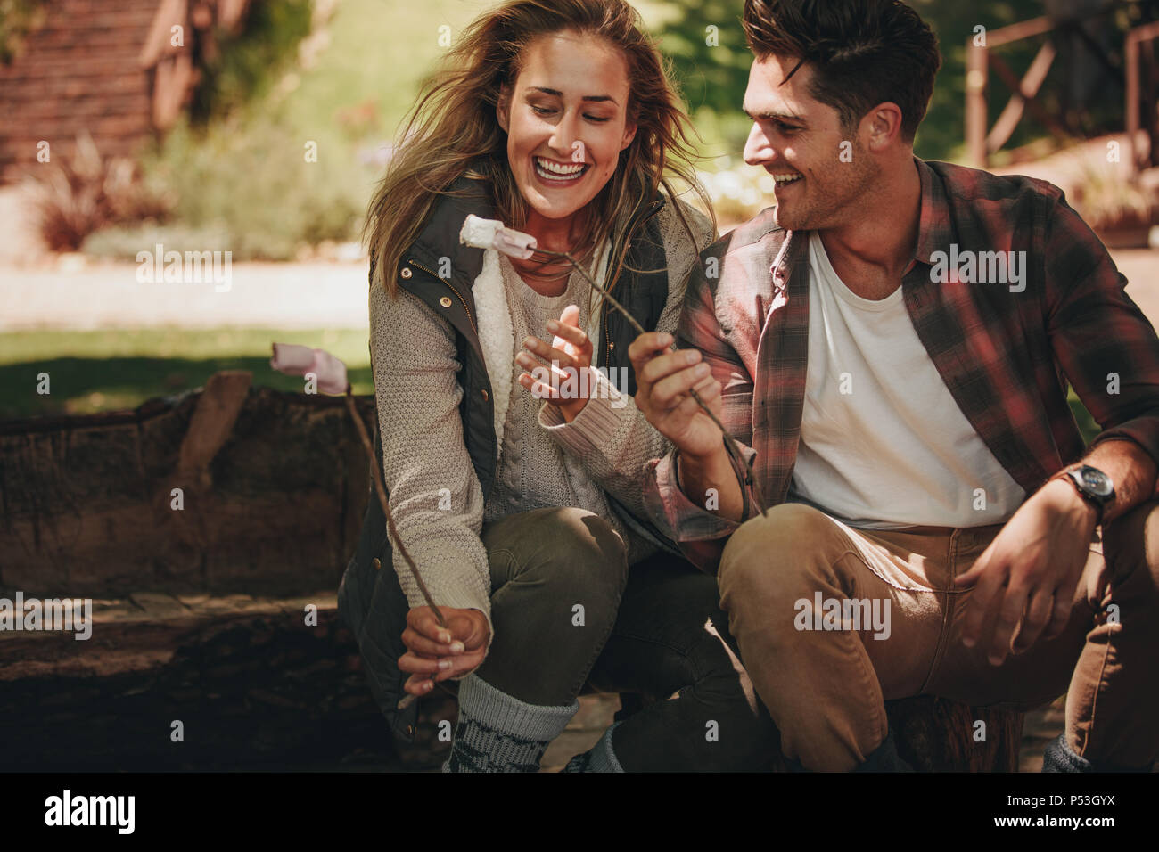 Smiling young camping couple eating roasted sweets. Man and woman having roasted marshmallows on camping. - Stock Image