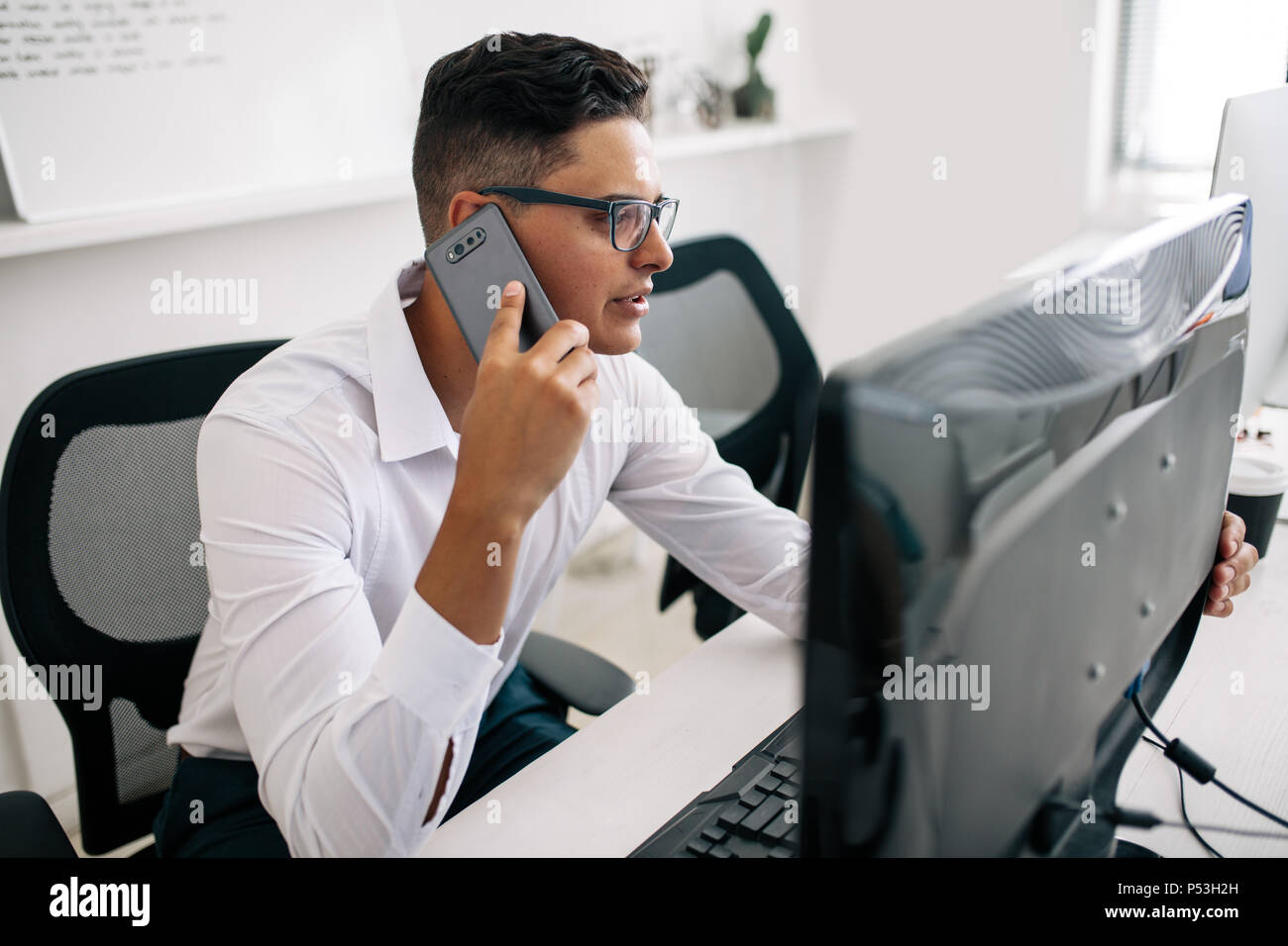 Software developer talking over mobile phone sitting at his office desk with a desktop computer in front. Man wearing spectacles working on desktop co - Stock Image