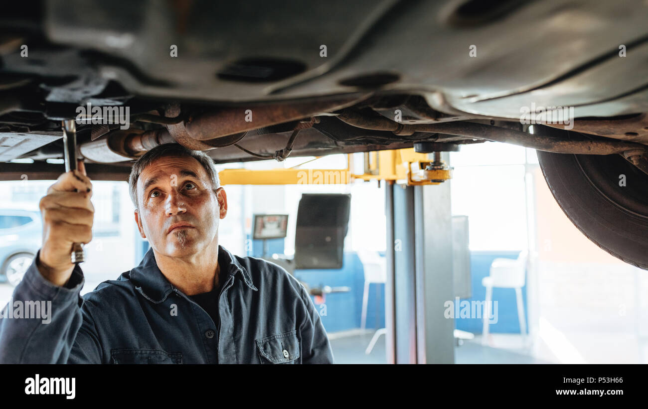Experienced car mechanic repairing a lifted car in garage. Auto repair men fixing exhaust system of a car. - Stock Image