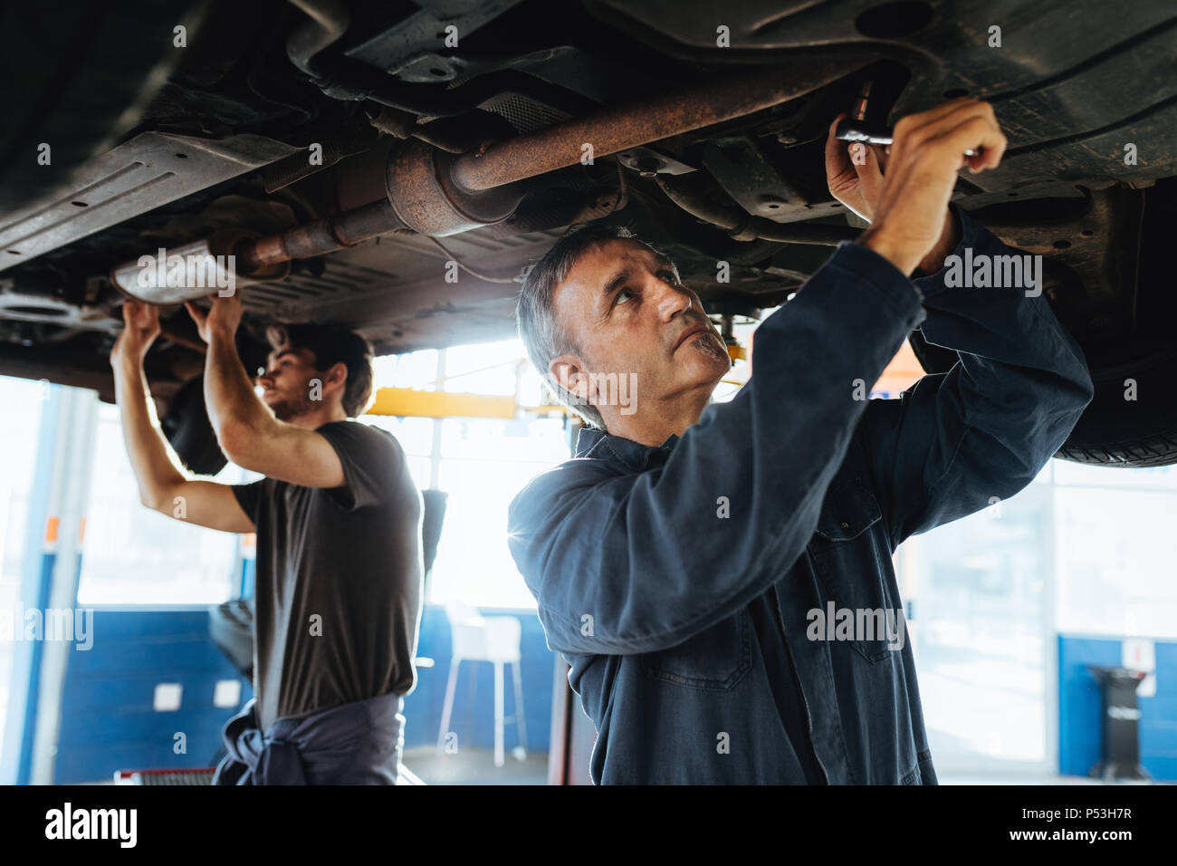 Two mechanics working under a car. Men in garage repairing exhaust system of a lifted automobile. - Stock Image
