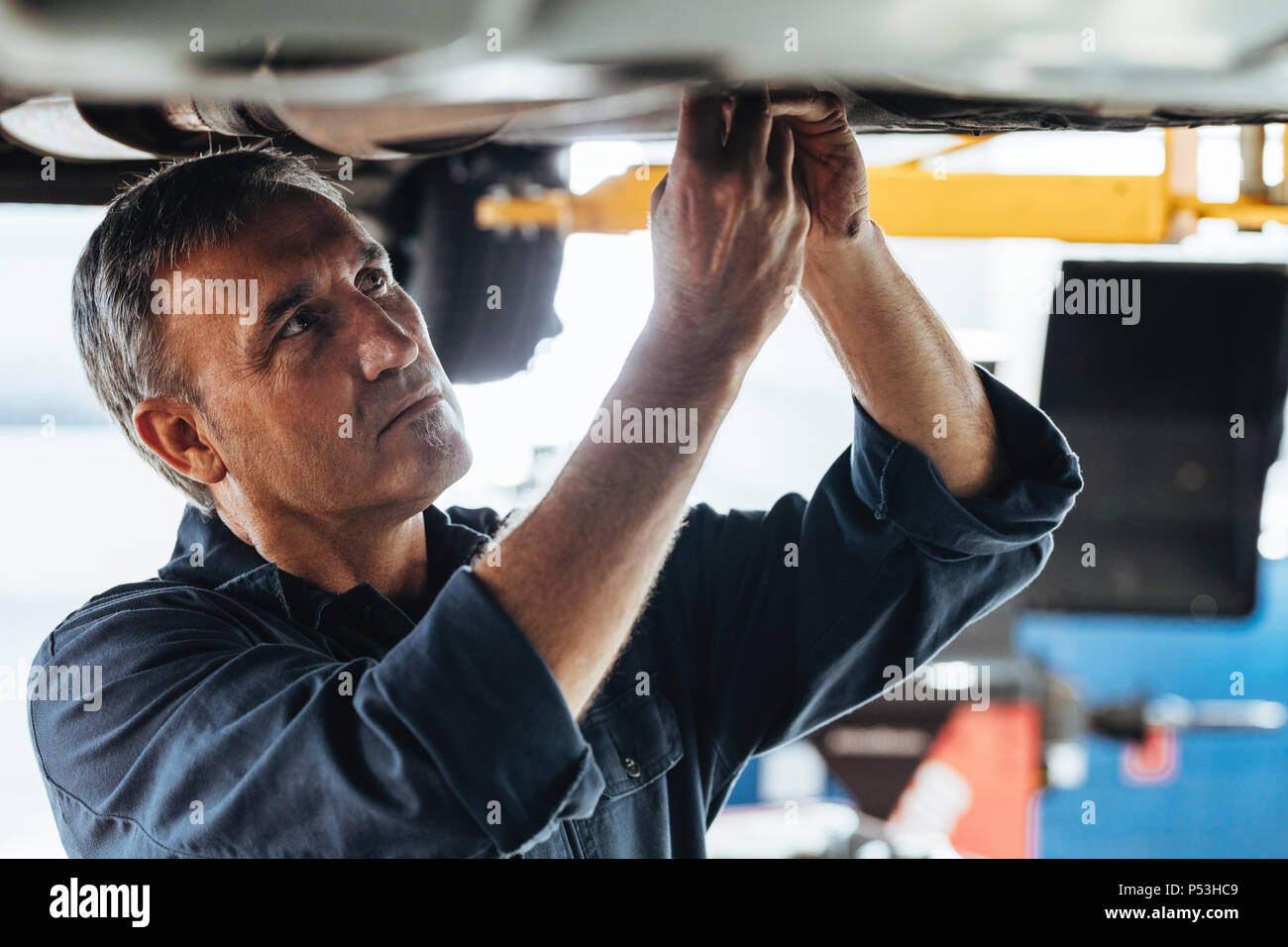 Car mechanic repairing a lifted car in garage. Auto repair men fixing a car in service station. - Stock Image
