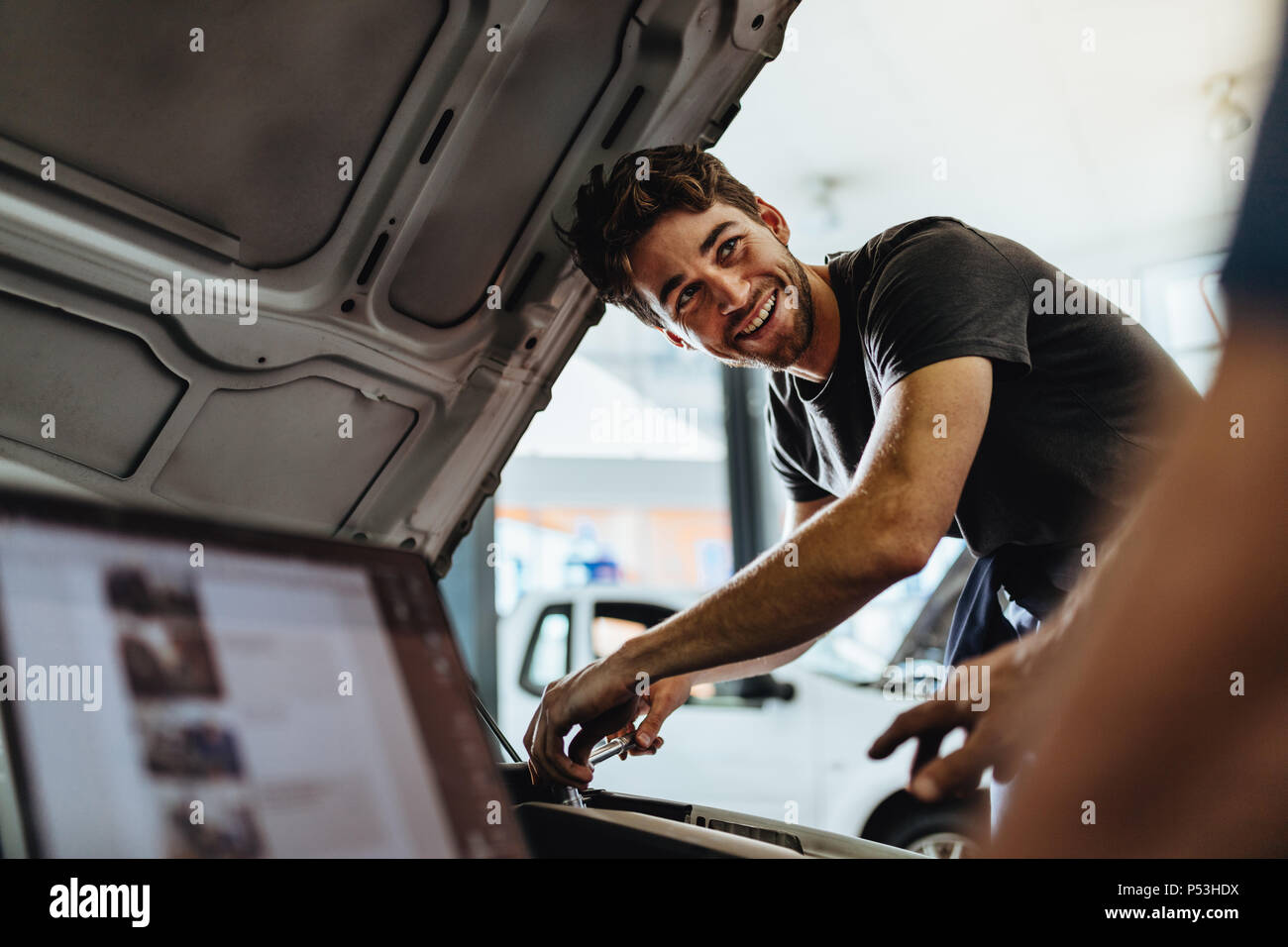 Auto mechanic fixing a vehicle in service station. Car mechanic working at automotive service center looking at his coworker and smiling. - Stock Image