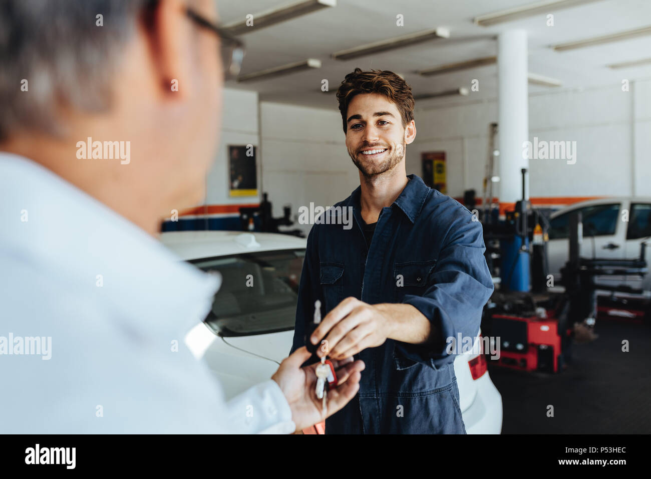 Car mechanic passing car keys to the car owner after repairing his vehicle. Mechanic giving car key to customer after servicing at garage. - Stock Image